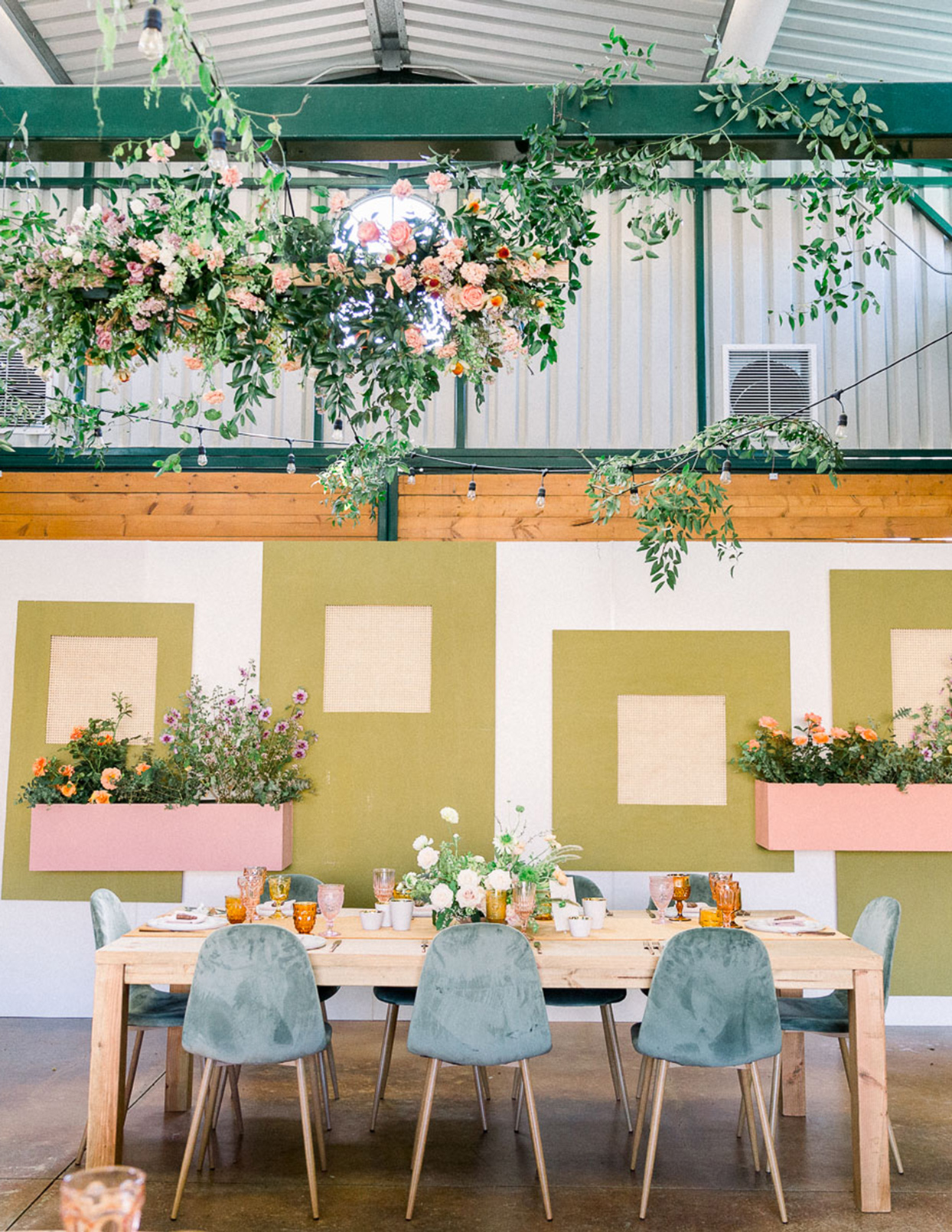 greenery with pastel colored flowers wooden table velvet chairs