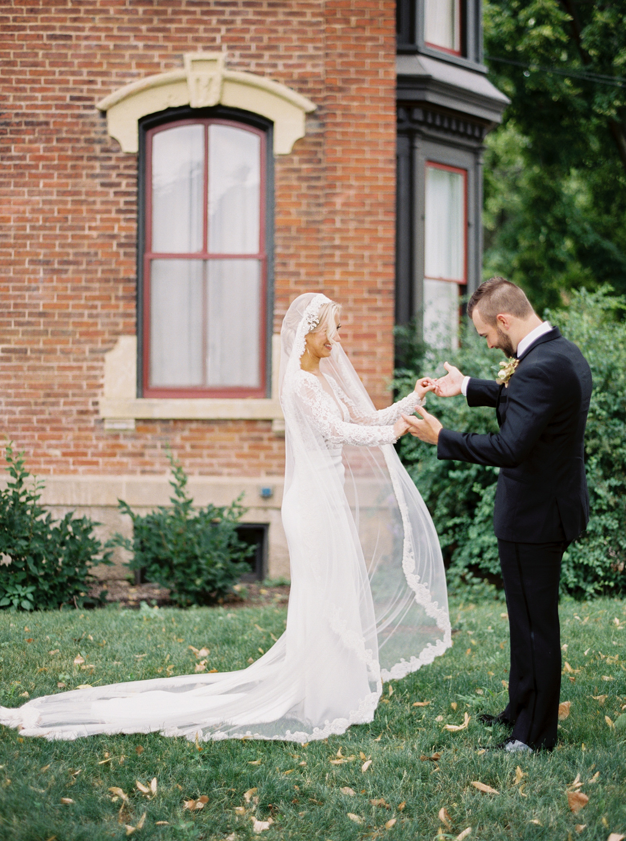 bride groom outdoors first look brick building