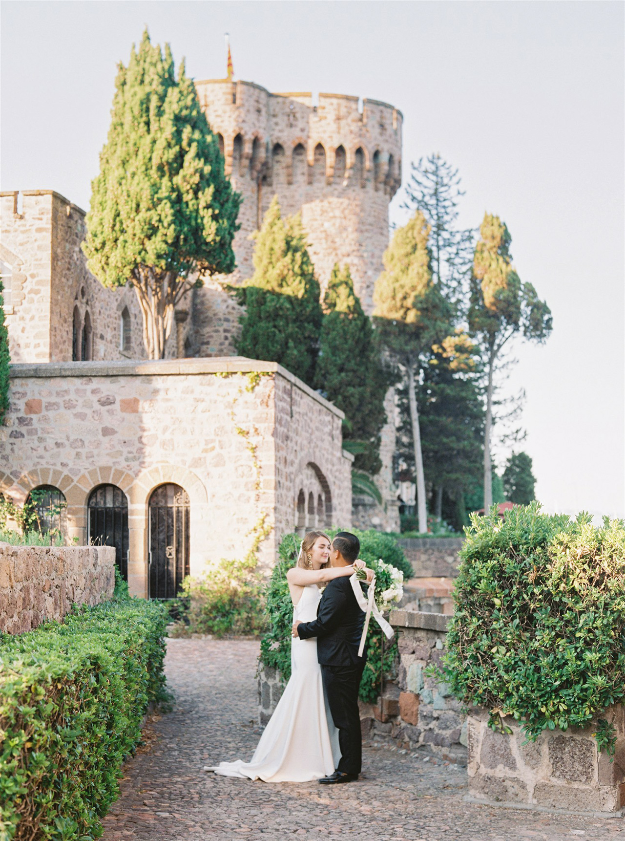 wedding couple pose outside historic castle