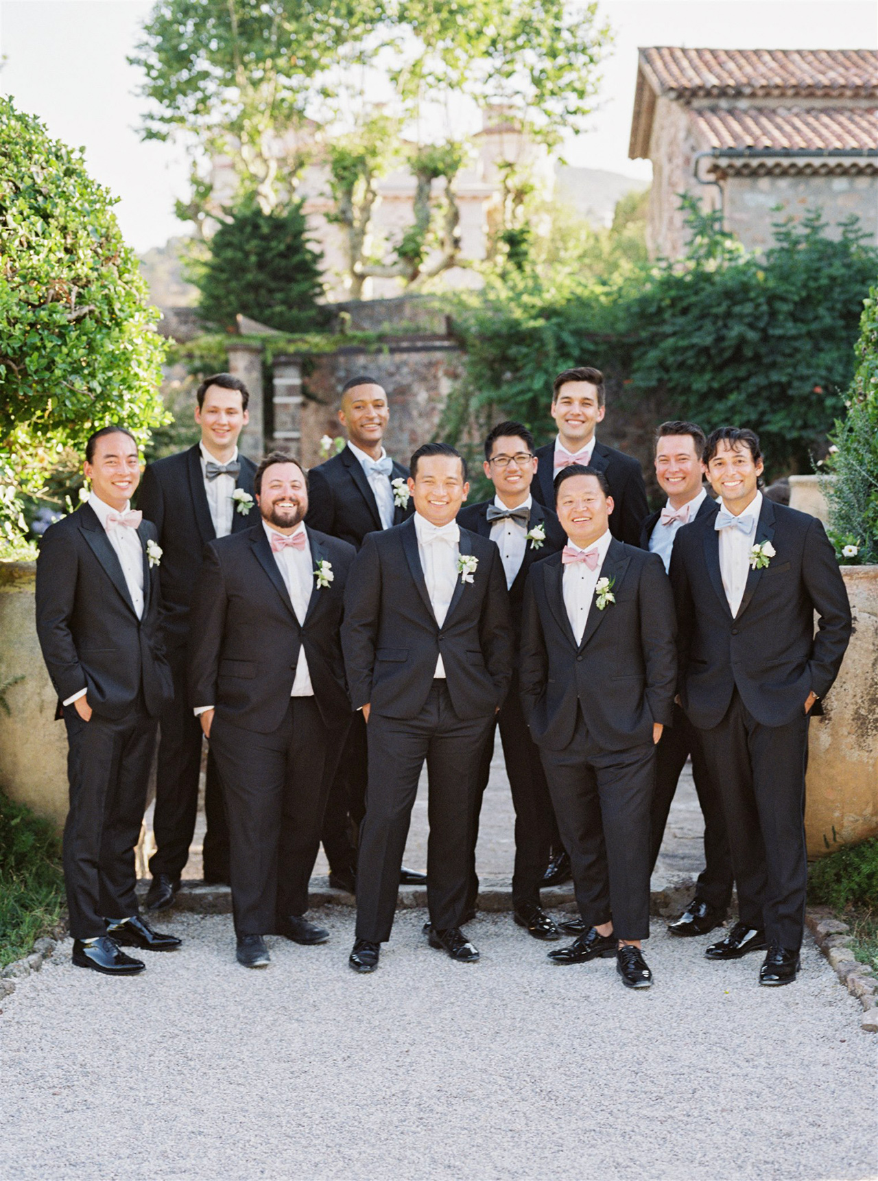 groom groomsmen pose outdoors tuxedos bowties