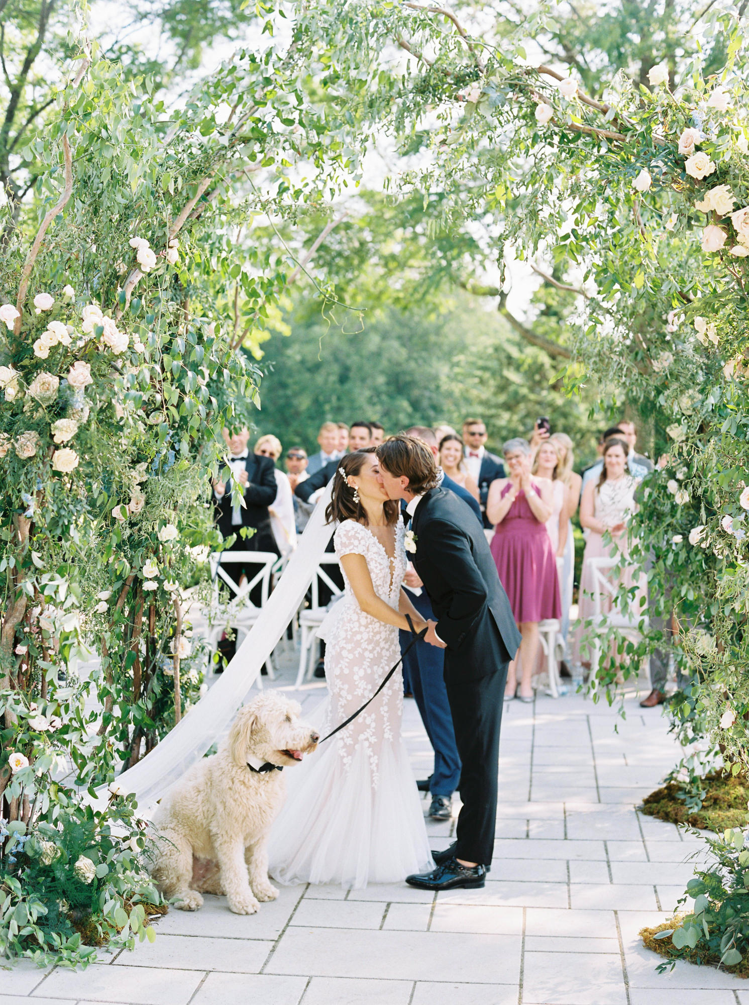 bride and groom kiss under greenery arch with dog