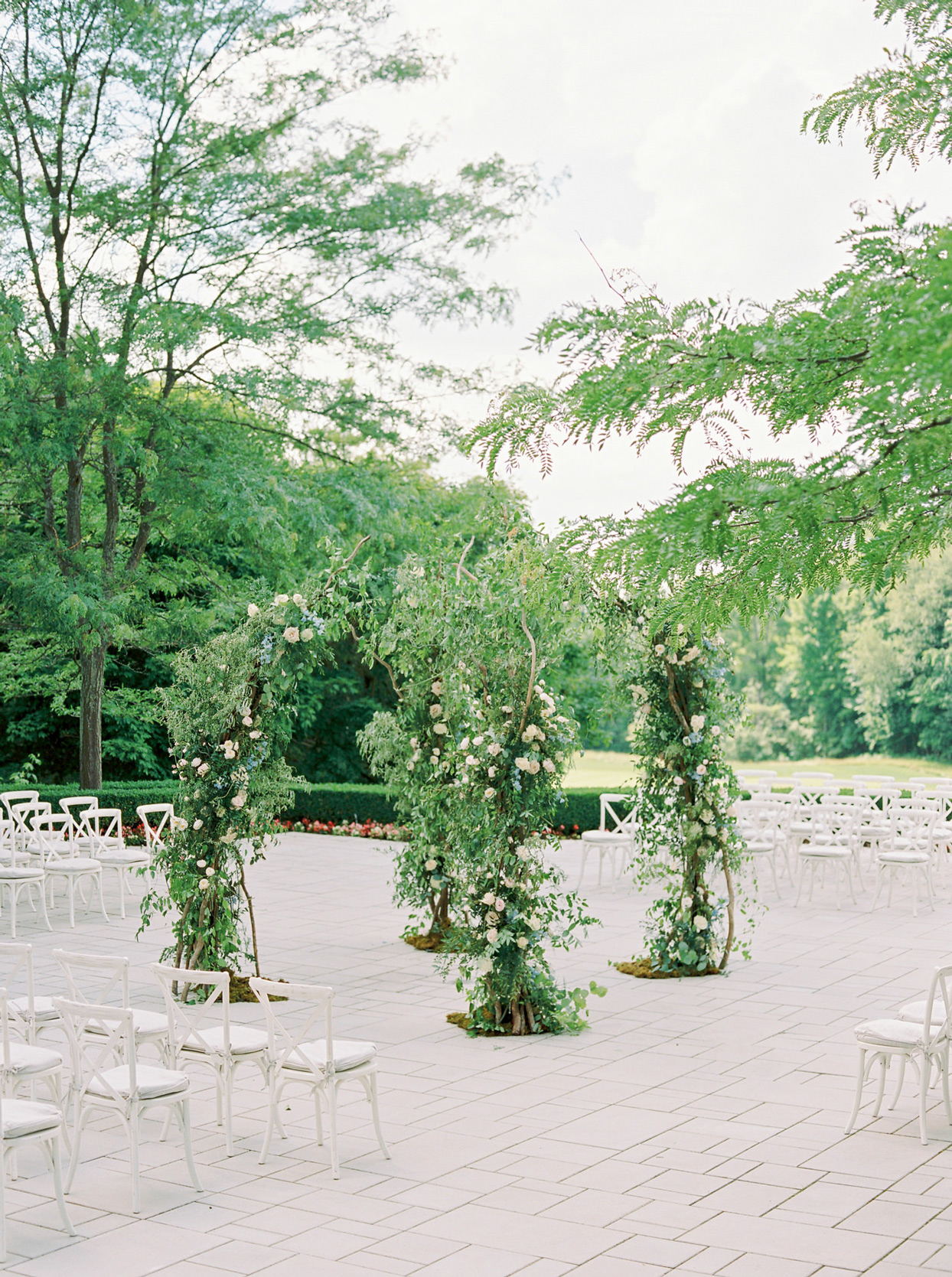 four pillar greenery arch with white chairs in a round ceremony setup