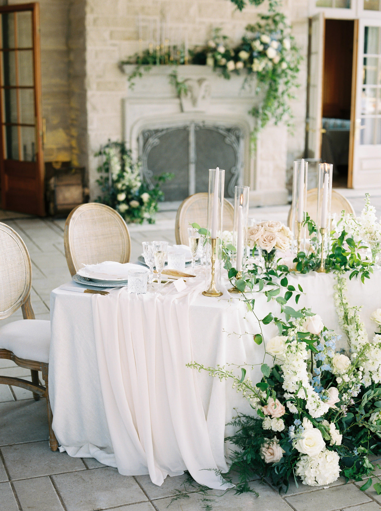 head table decorated with white and green floral arrangements