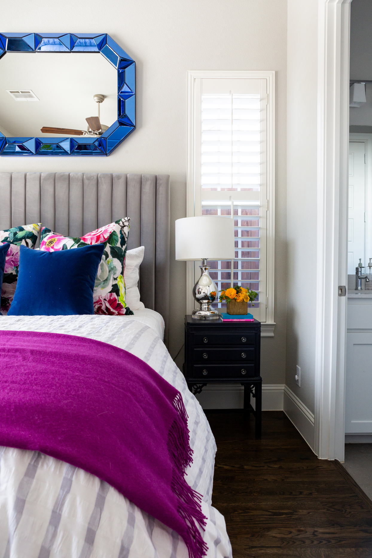 neutral-colored guest bedroom with jewel-toned accent pieces