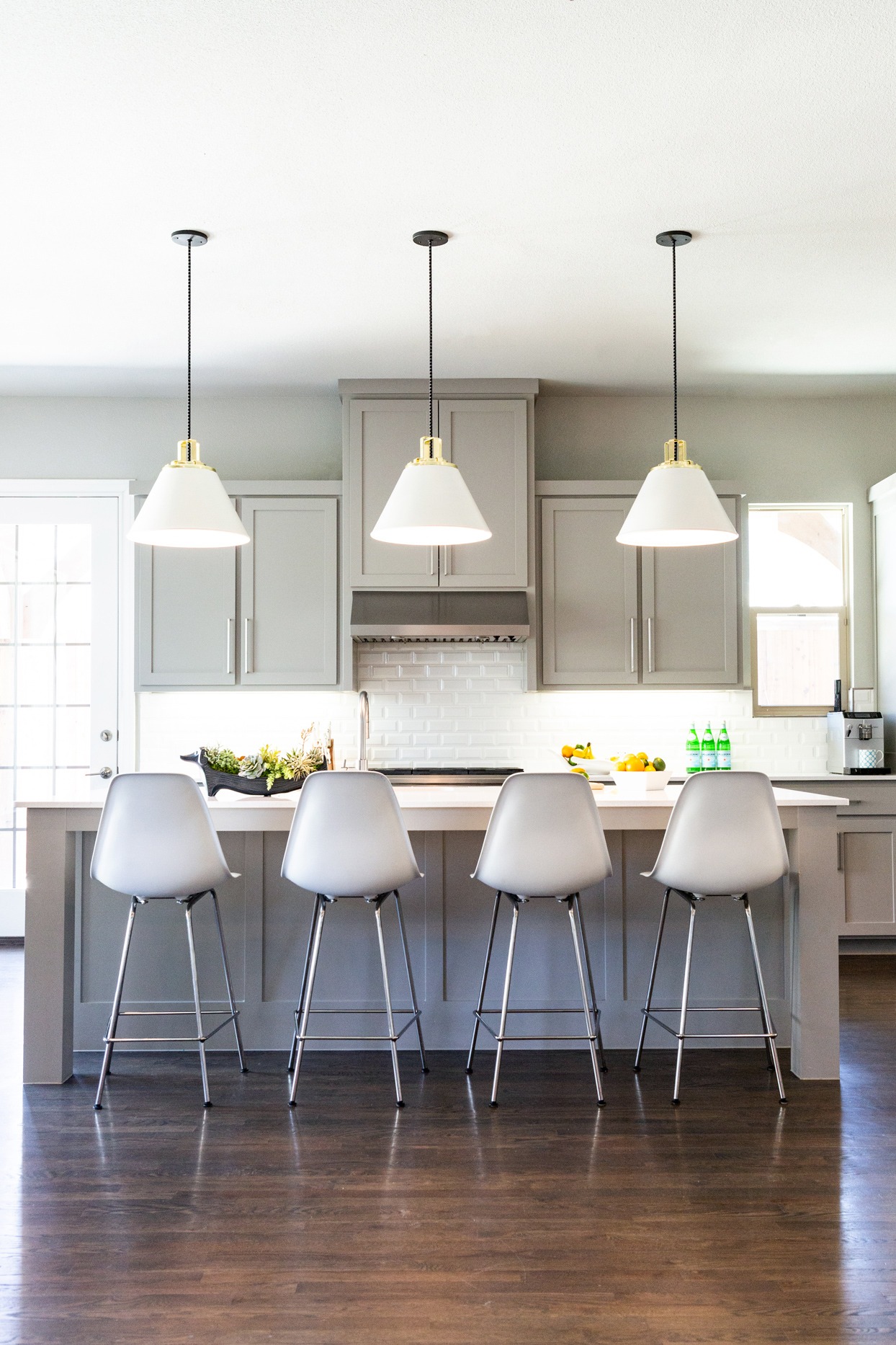 neutral-colored kitchen with white bar stools as island seating
