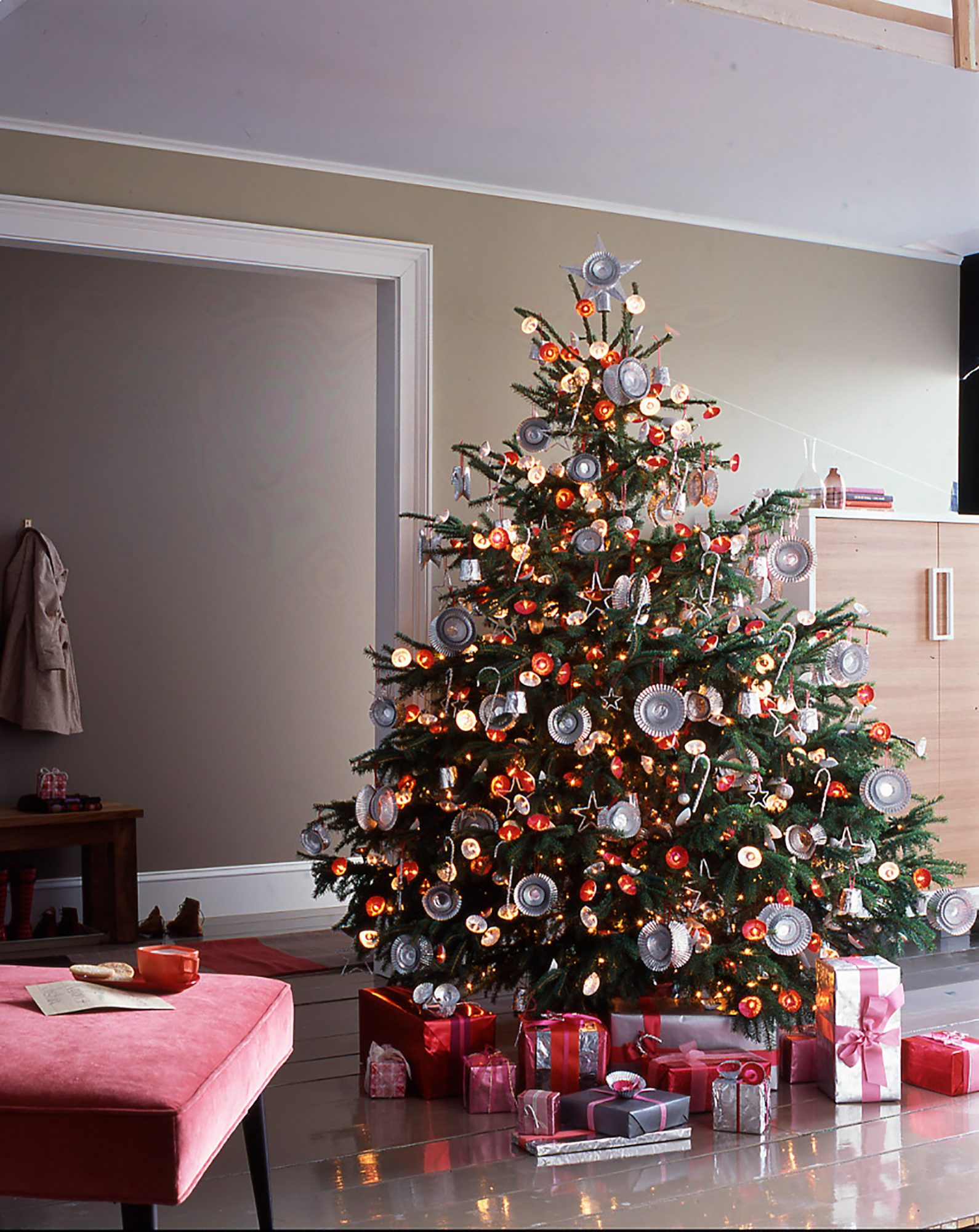 This tree gets its shimmer from aluminum foil. Sheets of foil are twisted and scrunched into stars, balls, and canes, all hung with yarn. Turn cupcake liners inside out; stack, and then glue back-to-back; tie on yarn to hang. Poke string lights through small liners for a radiant glow. More liners decorate a foil-covered cardboard star (with a toilet-paper tube back). A silver mouse sits atop shining gifts.Shop Now: GE String-a-Long Miniature Lights, $7, michaels.com. Celebrate It Standard Foil Baking Cups in Gold and Silver, $2 each, michaels.com.