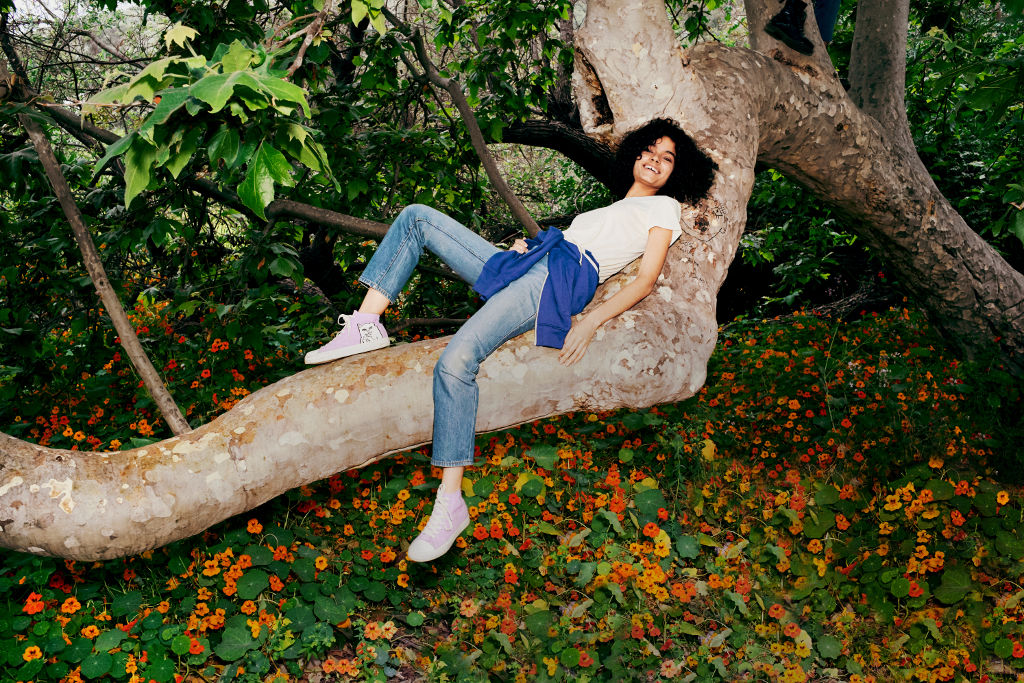 woman in jeans t-shirt lounging on tree branch