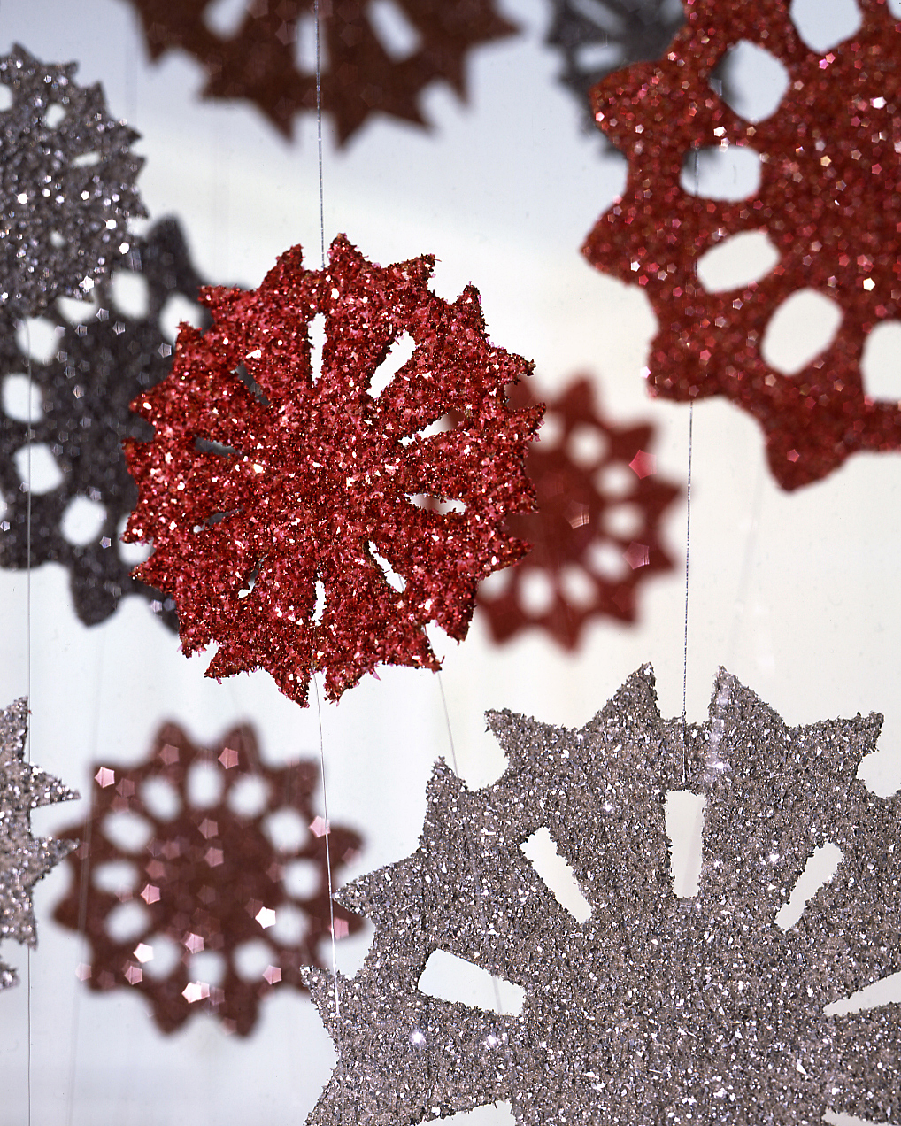 Tinsel isn't just for sprinkling on an evergreen tree. Try creating our sparkling ornaments to brighten any room. Begin by enlarging templates as desired with a copier—then tape these to a piece of heavy mat board or smooth cardboard, and place over a protective surface, like a self-healing mat. With a utility knife, cut through the layers to create your snowflake shape. Remove the template, and using a medium paintbrush, coat one side of the shape with craft glue. Sprinkle with fine glitter; let the glue dry, and shake off excess glitter. Repeat, using glass-shard glitter on both sides. Finally, attach silver thread and hang the snowflakes on your tree with removable adhesive hooks.Shop Now: Martha Stewart Collection Jewel Glitter Set, $14, michaels.com. Creatology Crystal Clear Glitter, $7 for 12 ounces, michaels.com. Martha Stewart Collection Swivel Cutting Knife, $13, michaels.com. Creatology Brown Corrugated Paper Board, $4.49, michaels.com.