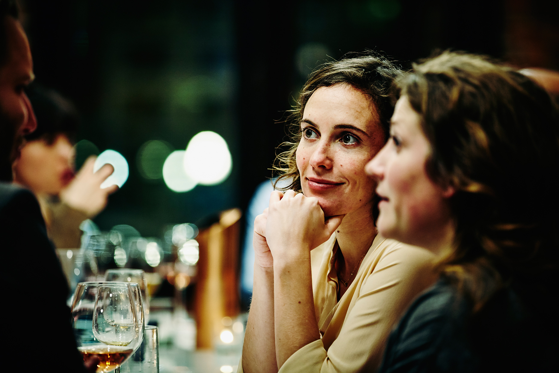 woman smiling and putting elbows on table