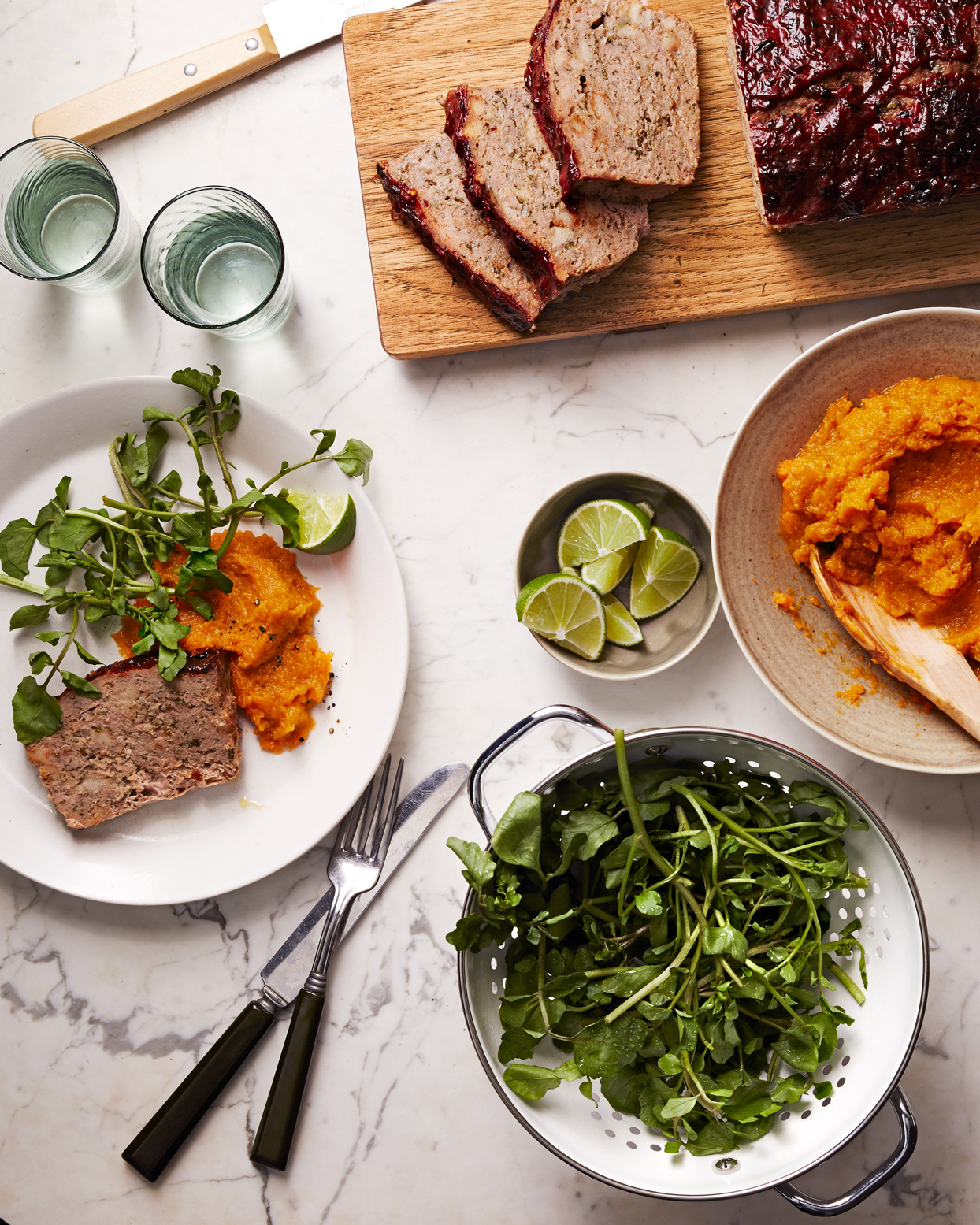meatloaf, mashed sweet potatoes, and greens on white marble tabletop