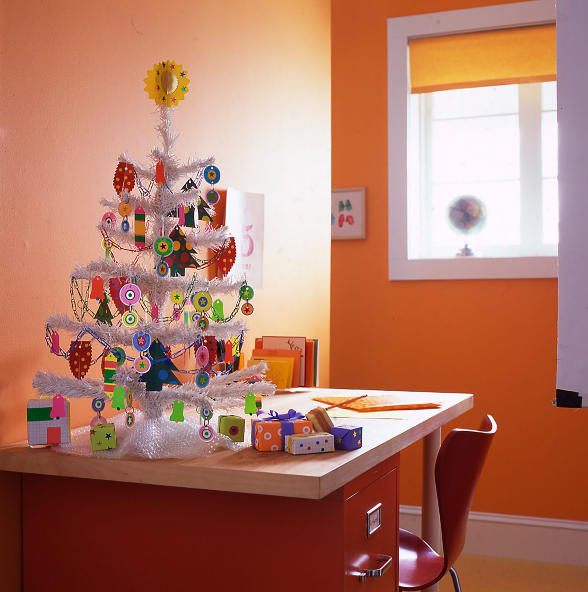 """Office-supply stores have all the trimmings for a tree that belies its workaday origins. Key tags decorated with stickers, ornaments cut from file folders, and paper-clip chains dangle from the branches. A bubble-packaging tree skirt and presents dressed up in graph paper, stickers, and rubber bands circle the base.Shop Now: Staples 5/16"""" Bubble Roll, $8, staples.com. Staples Smooth Paper Clips, $2 for 100, staples.com. HoneyWell Colored Key Tags, $10 for 20, staples.com."""