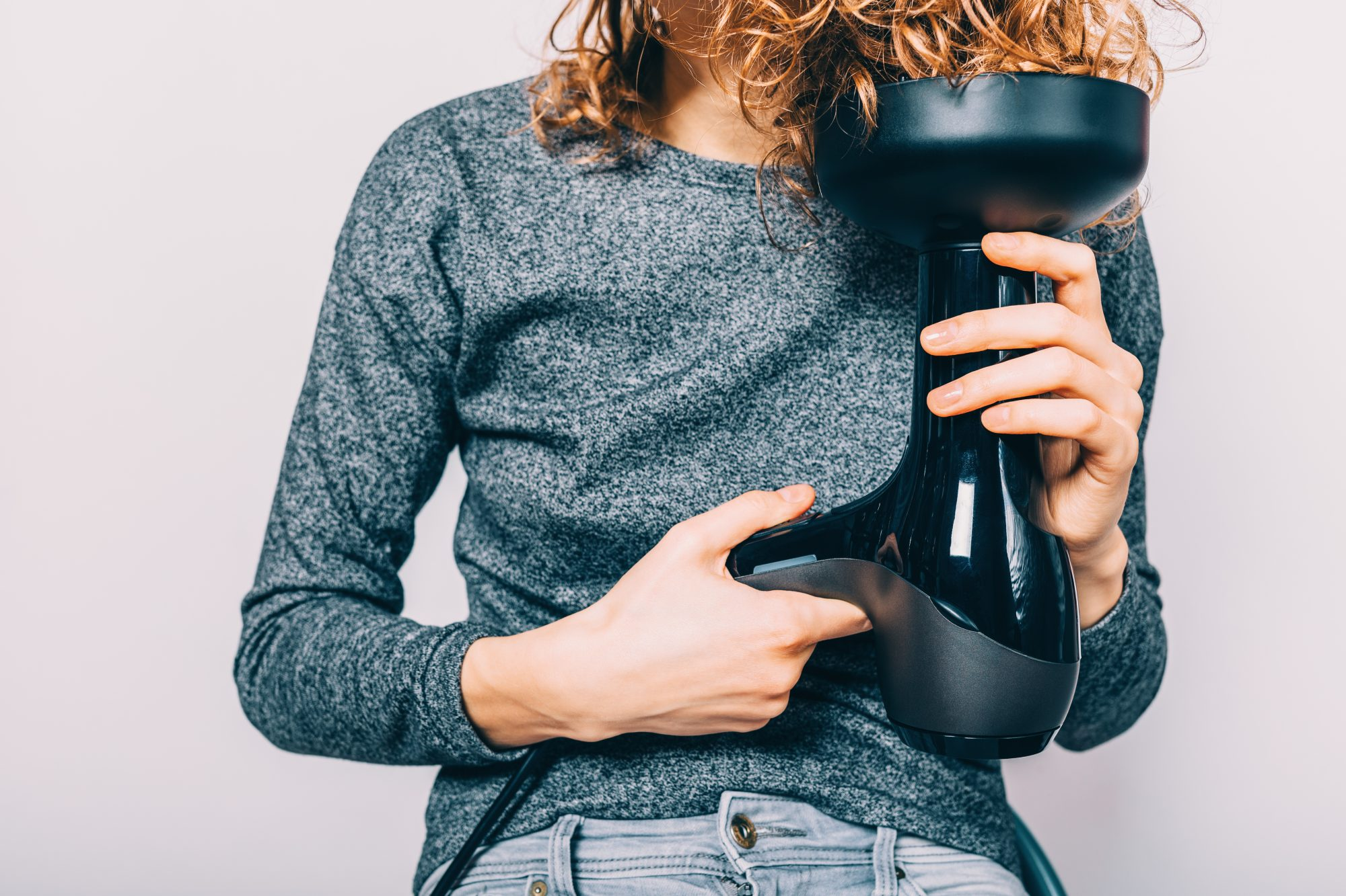 woman blow drying hair with diffuser