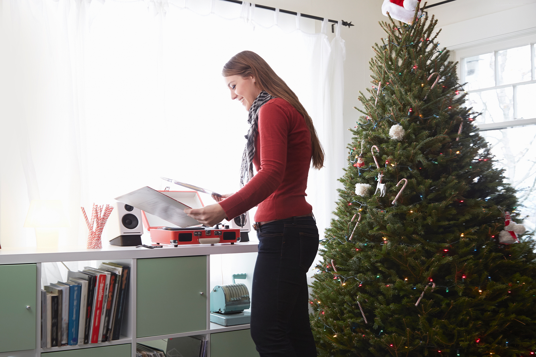 Person looking through records next to Christmas tree