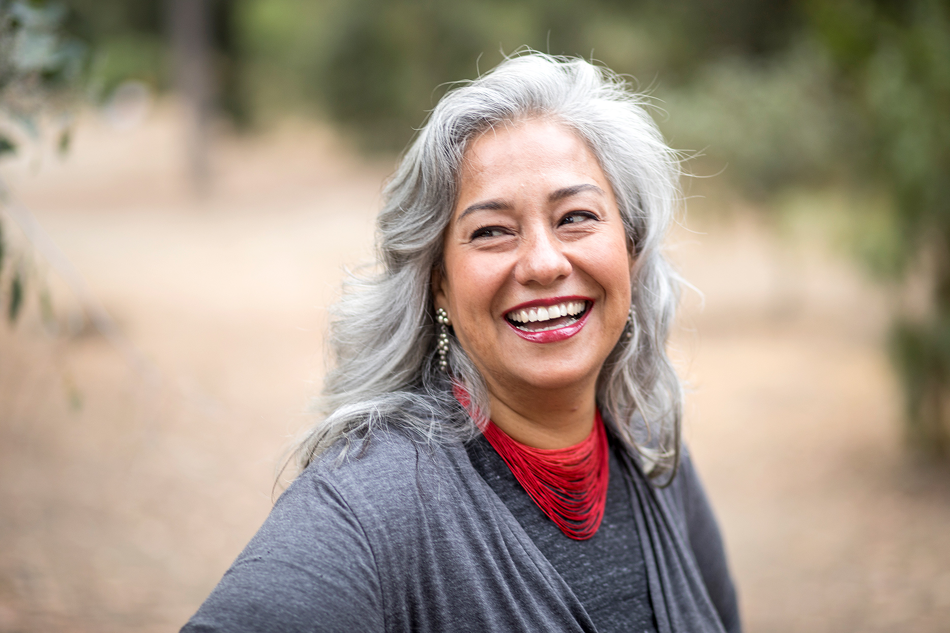 smiling middle-aged woman with silver hair and red necklace