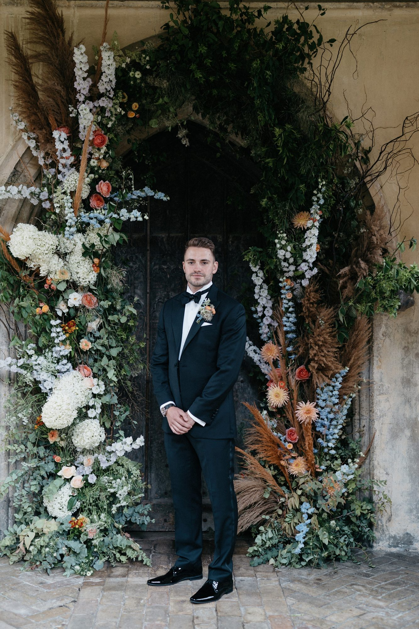 laurie lee wedding groom surrounded by floral decor