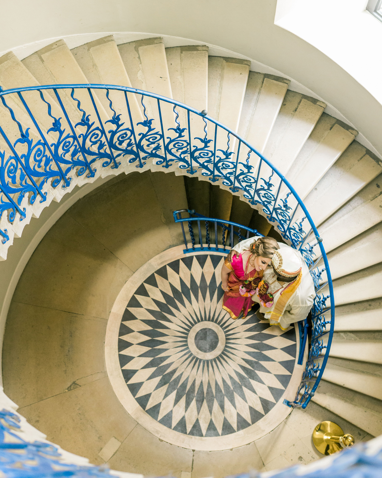 bride and grooms standing in spiral staircase with blue hand railing
