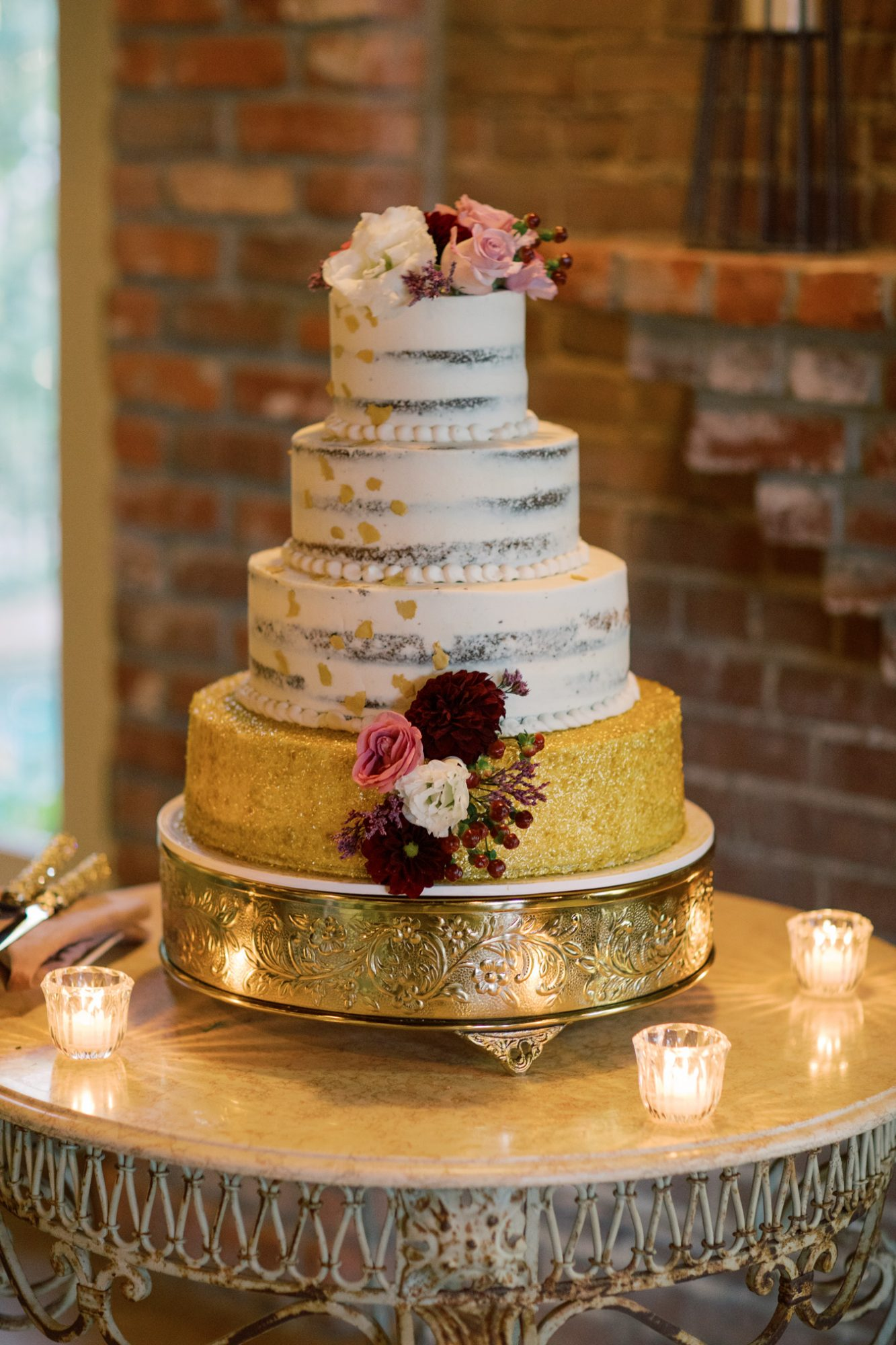 4-tier wedding cake with gold glitter base layer