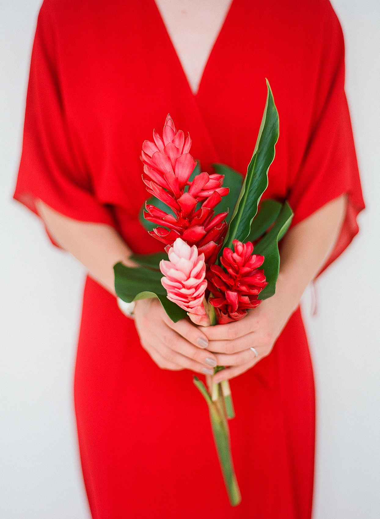 kelly sanjiv wedding bridesmaid in red dress holding floral bouquet