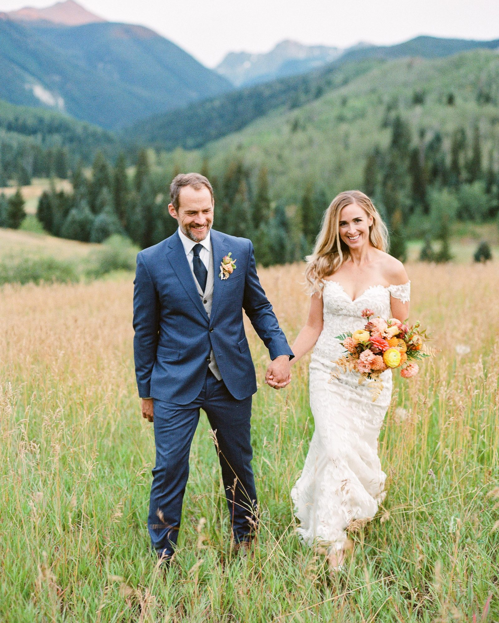 jill phil wedding couple walk in grass field with mountain view