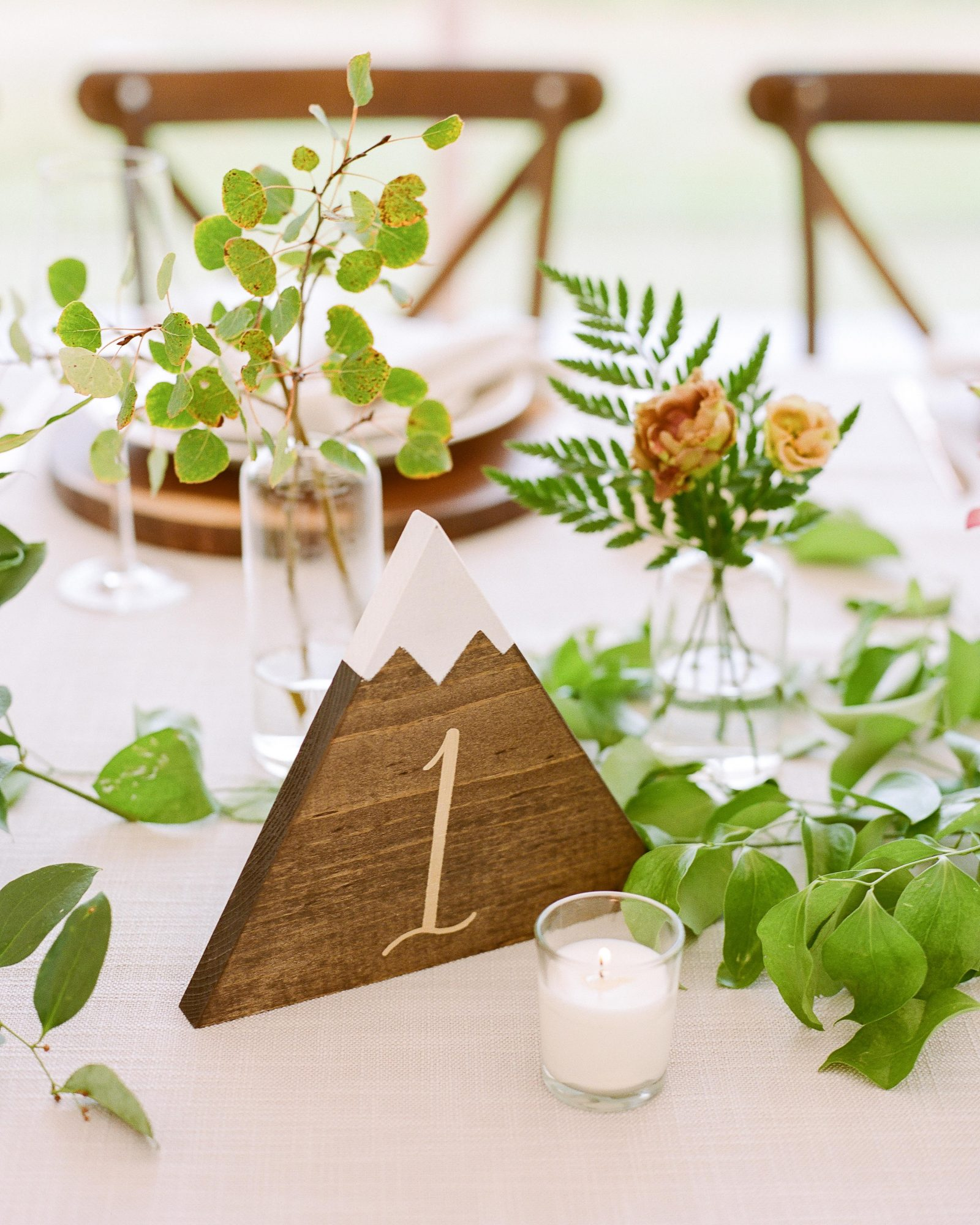 jill phil wedding wooden table number with mountain design surrounded by plant decor