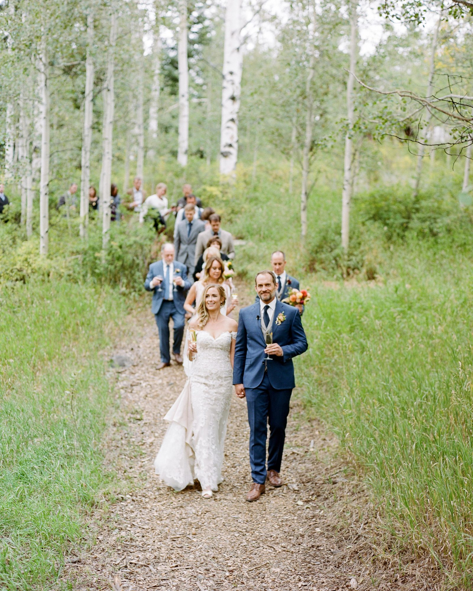 jill phil wedding couple and guests walking through wooded area