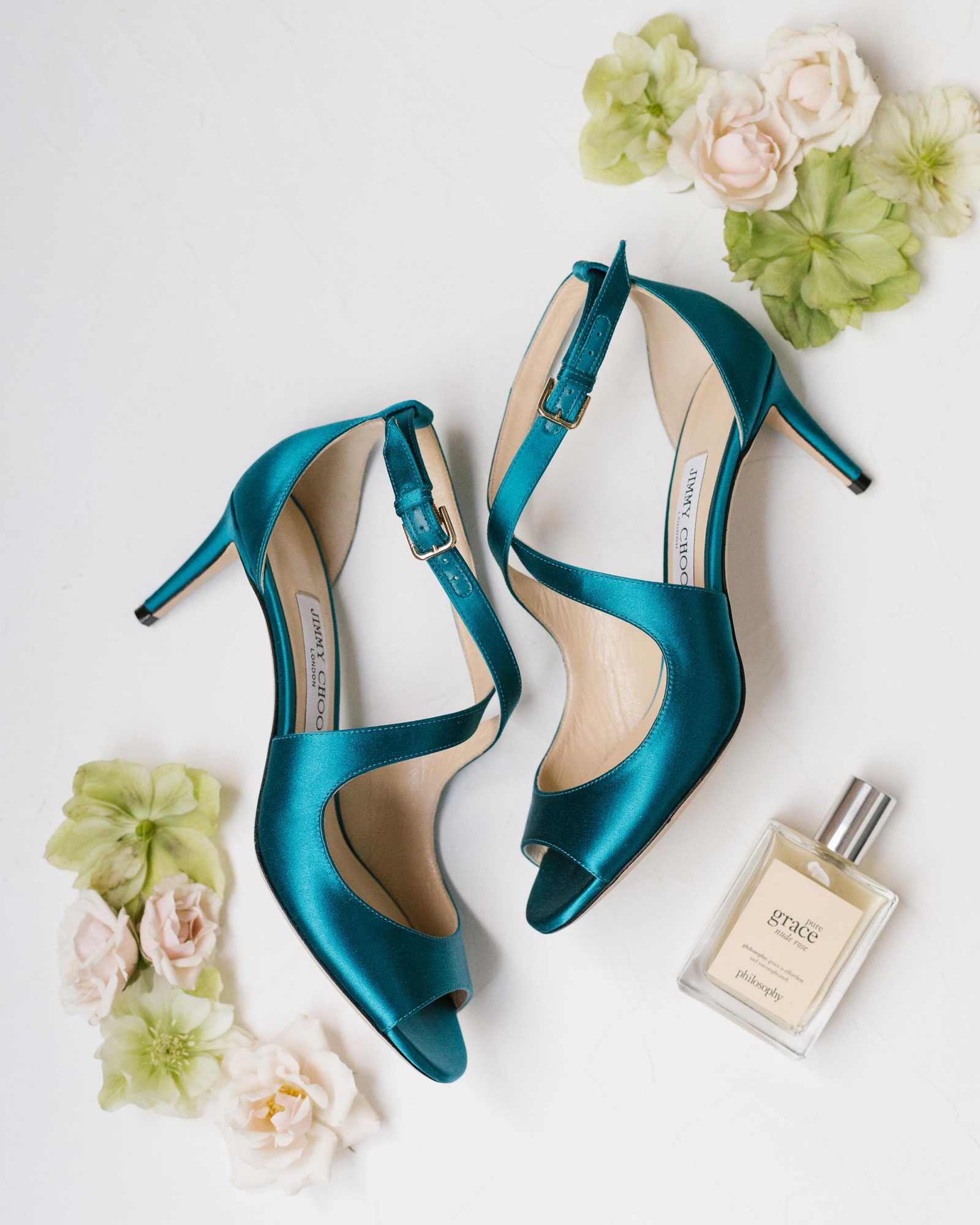 shelana kevin wedding bride teal heels surrounded by flowers and a fragrance bottle