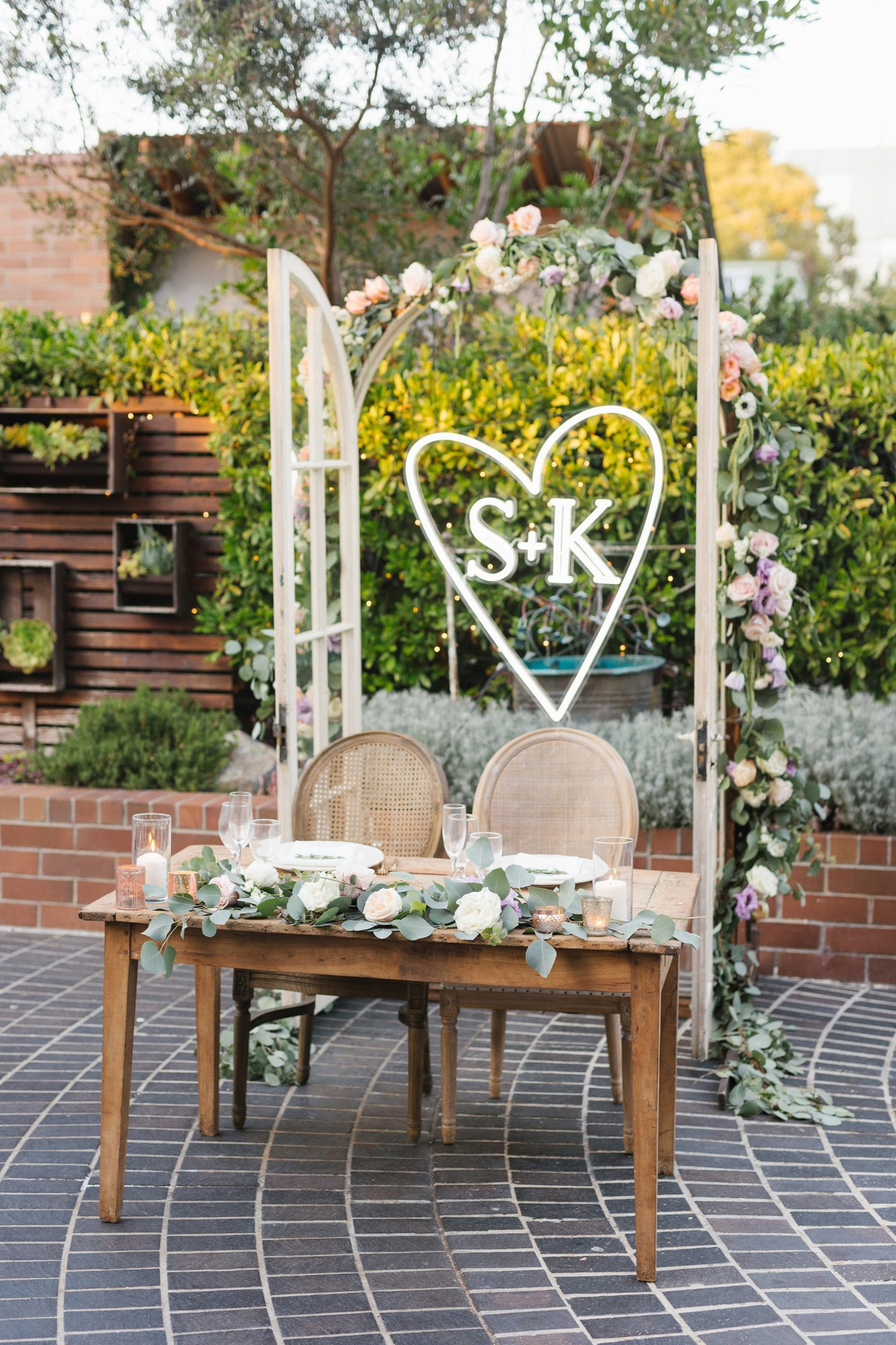 shelana kevin wedding couple reception table decorated with flowers and a door backdrop