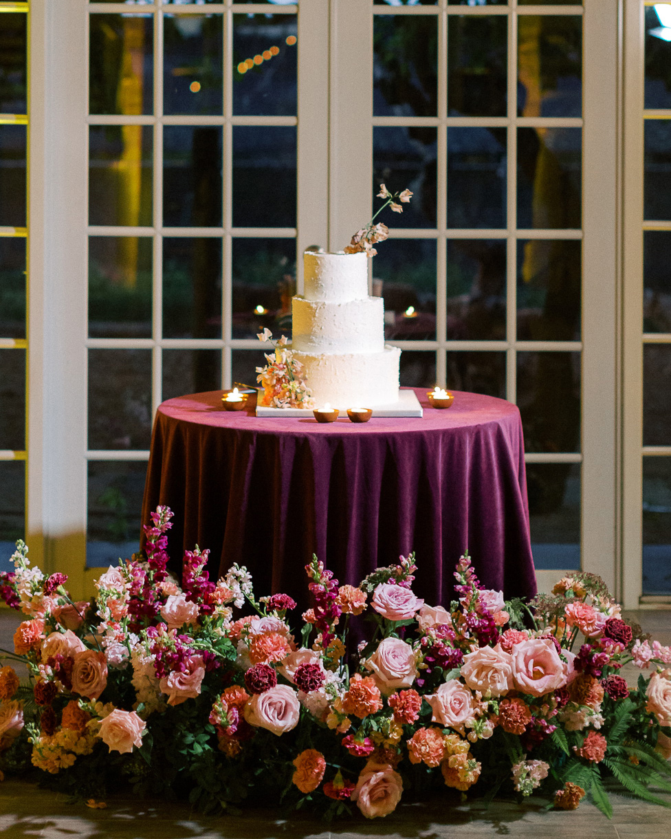 melissa lindsey wedding cake on maroon clothed table floral decor