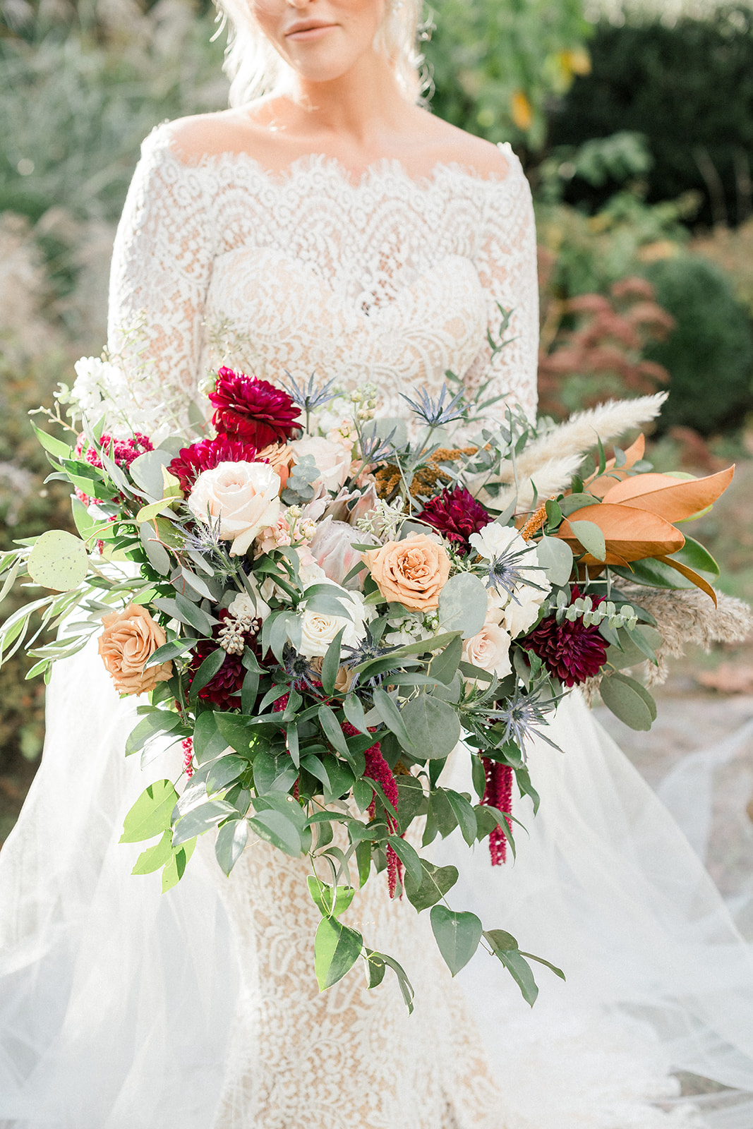 bride holding large greenery and floral bouquet