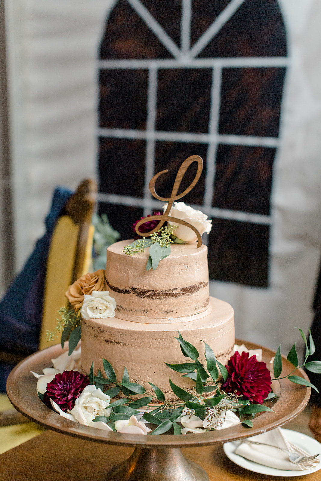 two tiered peach colored frosting wedding cake with floral accent