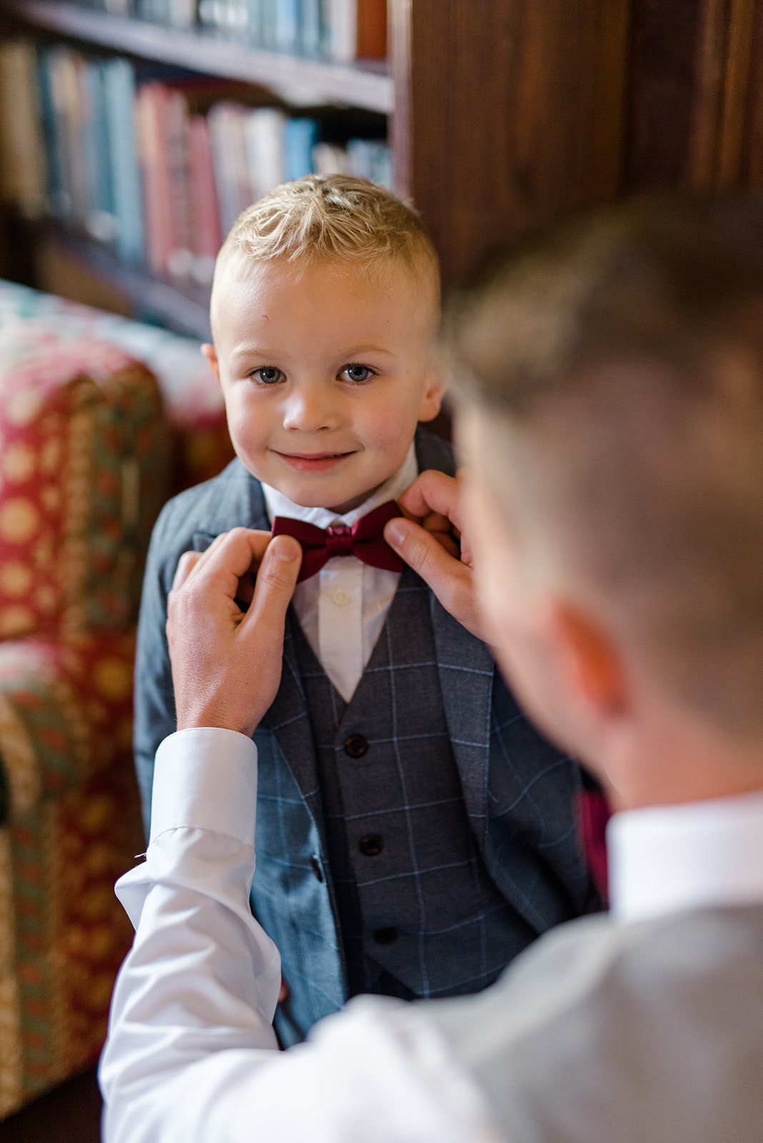 groom putting bow tie on son
