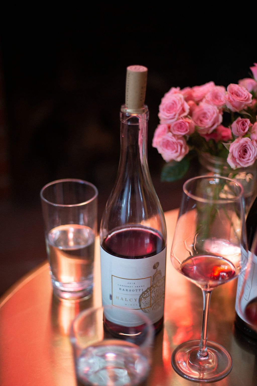 wine bottle, glasses, and roses on table