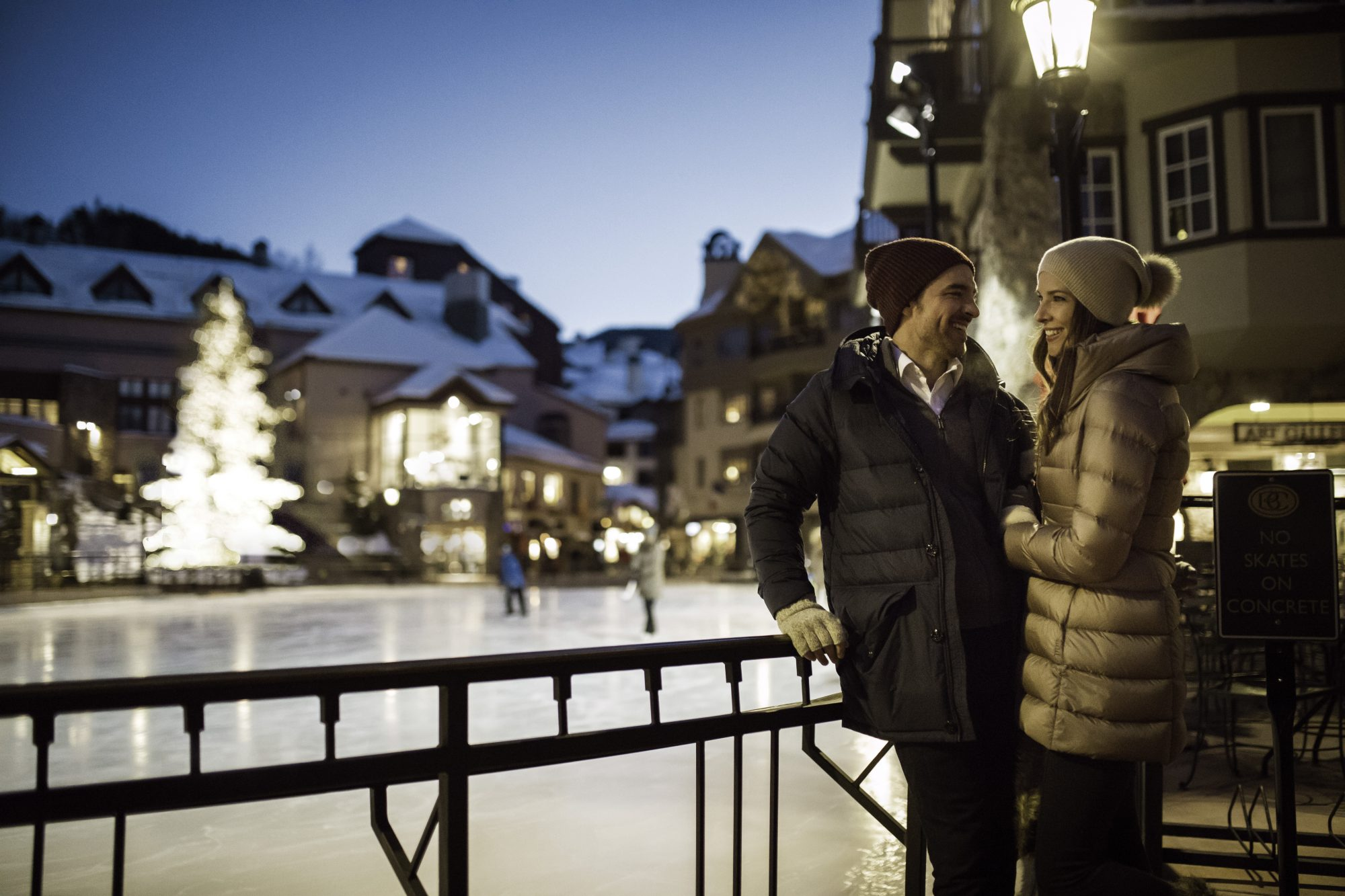 Couple enjoys ice rink in the village (with tree) in Beaver Creek, CO.