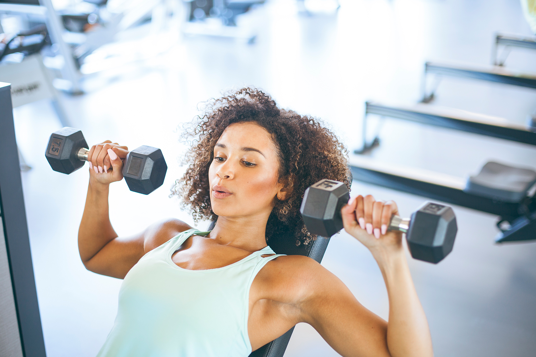 woman in tank lifting free weights at gym