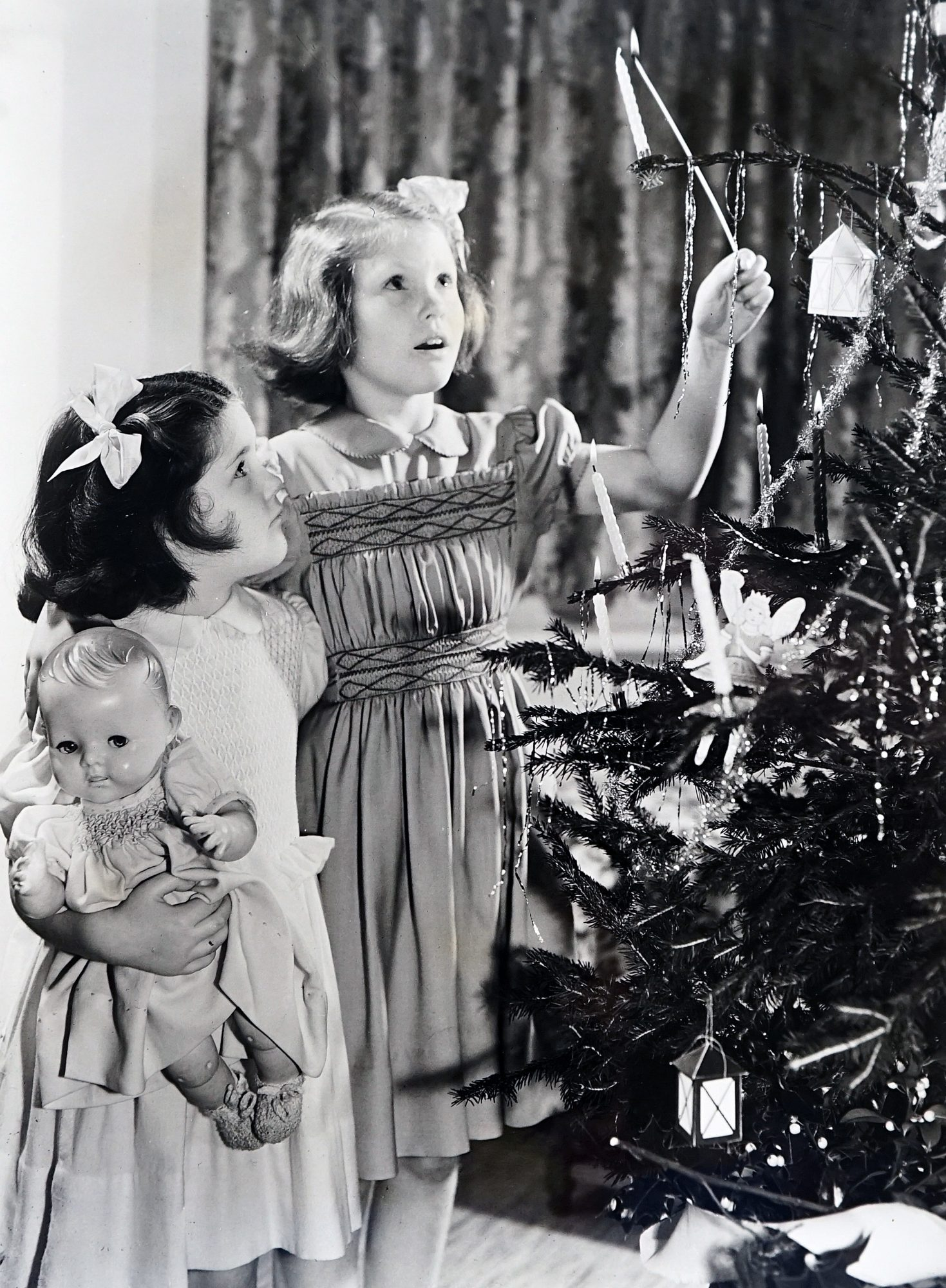 Photograph of children lighting the candles on the Christmas tree