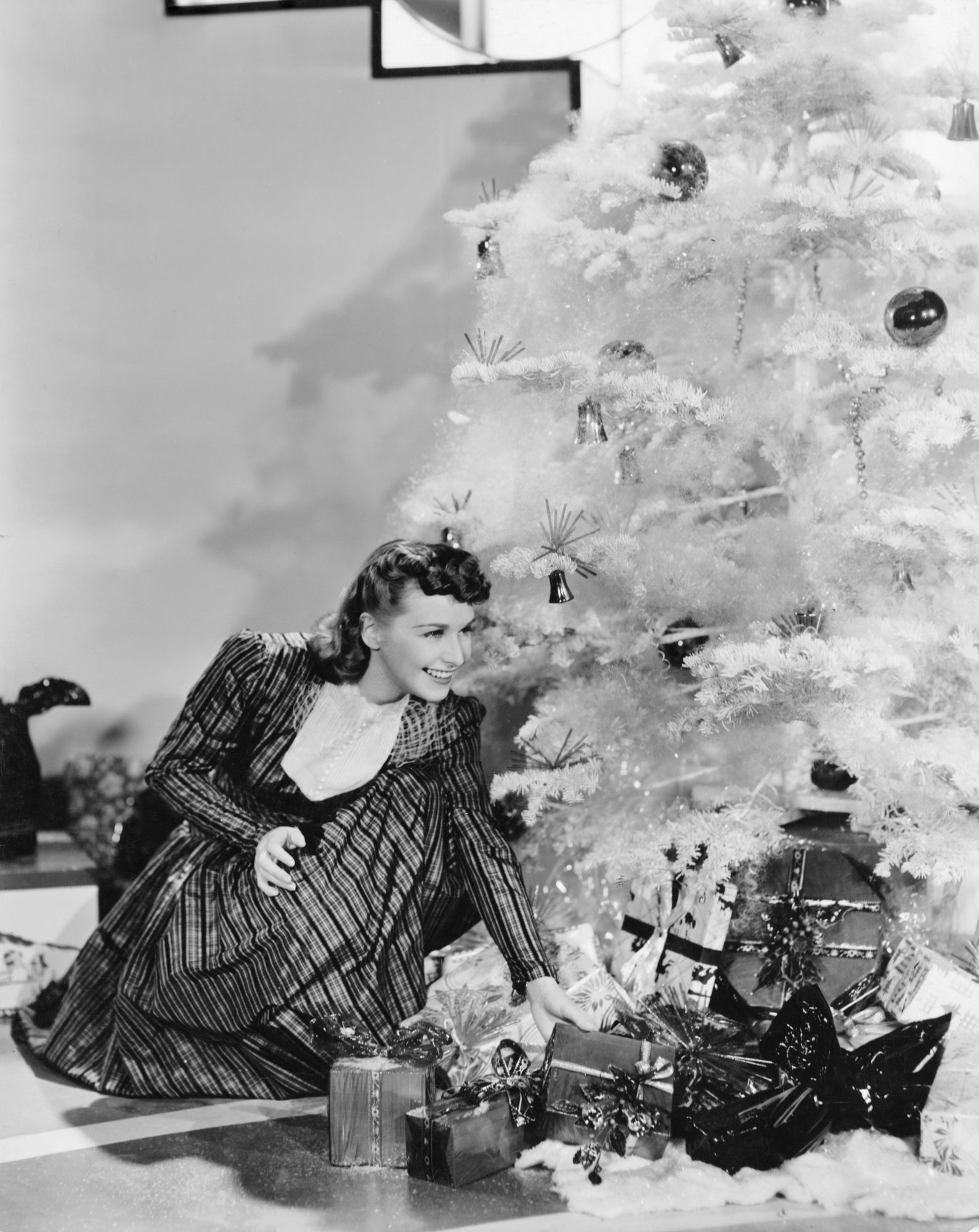 American actress and singer Rosemary Lane (1913 - 1974) of the Lane Sisters, with a pile of Christmas presents under the tree
