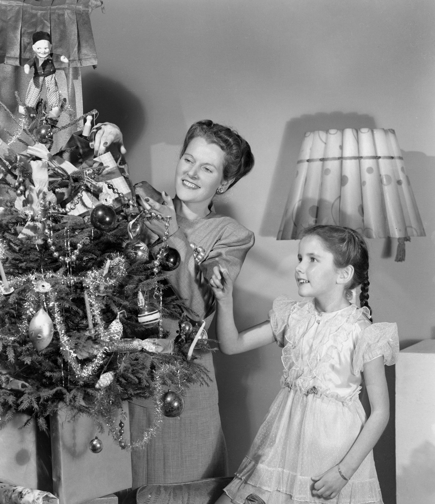 The Shiny Brite company produced the most popular Christmas tree ornaments in the United States throughout the 1940s—a great selling point during World War II. In early years, wartime production necessitated the replacement of the ornament's metal cap with a cardboardtab, from which the owner would useyarnorstring to hang the ornament.                                       Pictured here: Mother and daughter decorate their Christmas tree together. By this time, it was a tradition for many homes to trim the tree as a family. Tinsel garlands are draped around toys, bulb ornaments, and a toy topper for the tree.