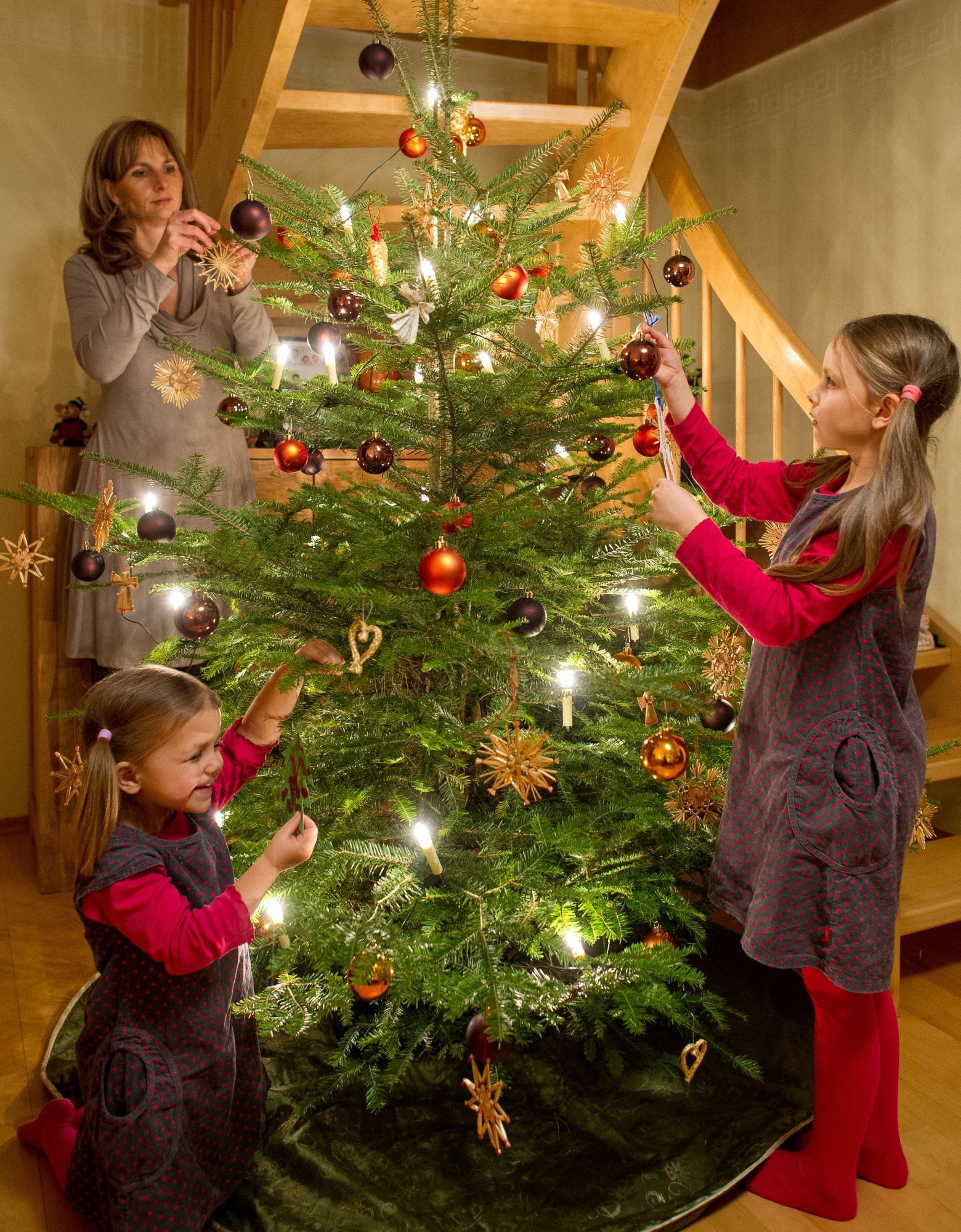 mother and daughters decorate the Christmas tree