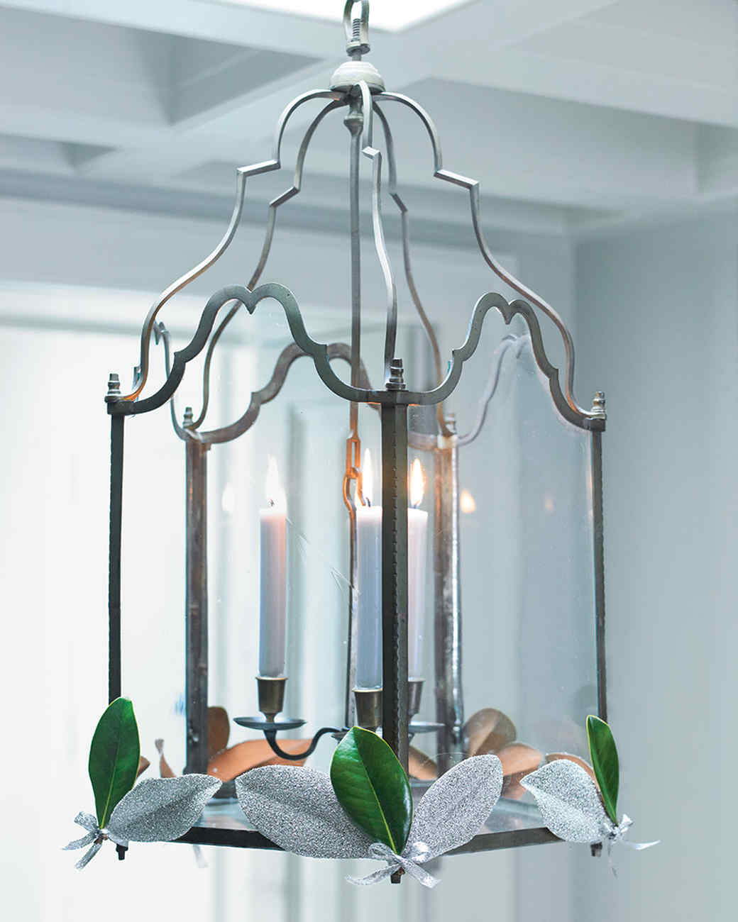 holiday lantern with candles and magnolia leaves