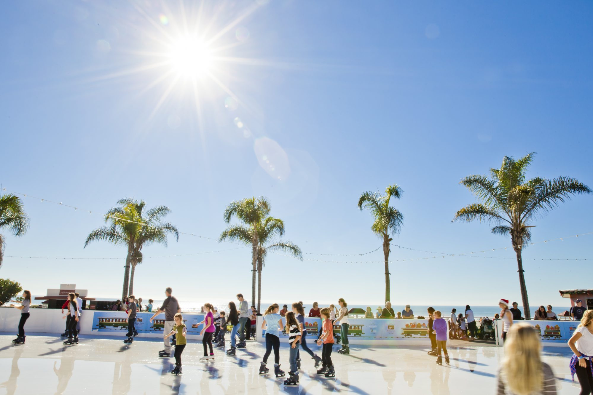 Children and adults ice skating on an outdoor ice rink at the historic Hotel Del Coronado next to the Pacific Ocean.