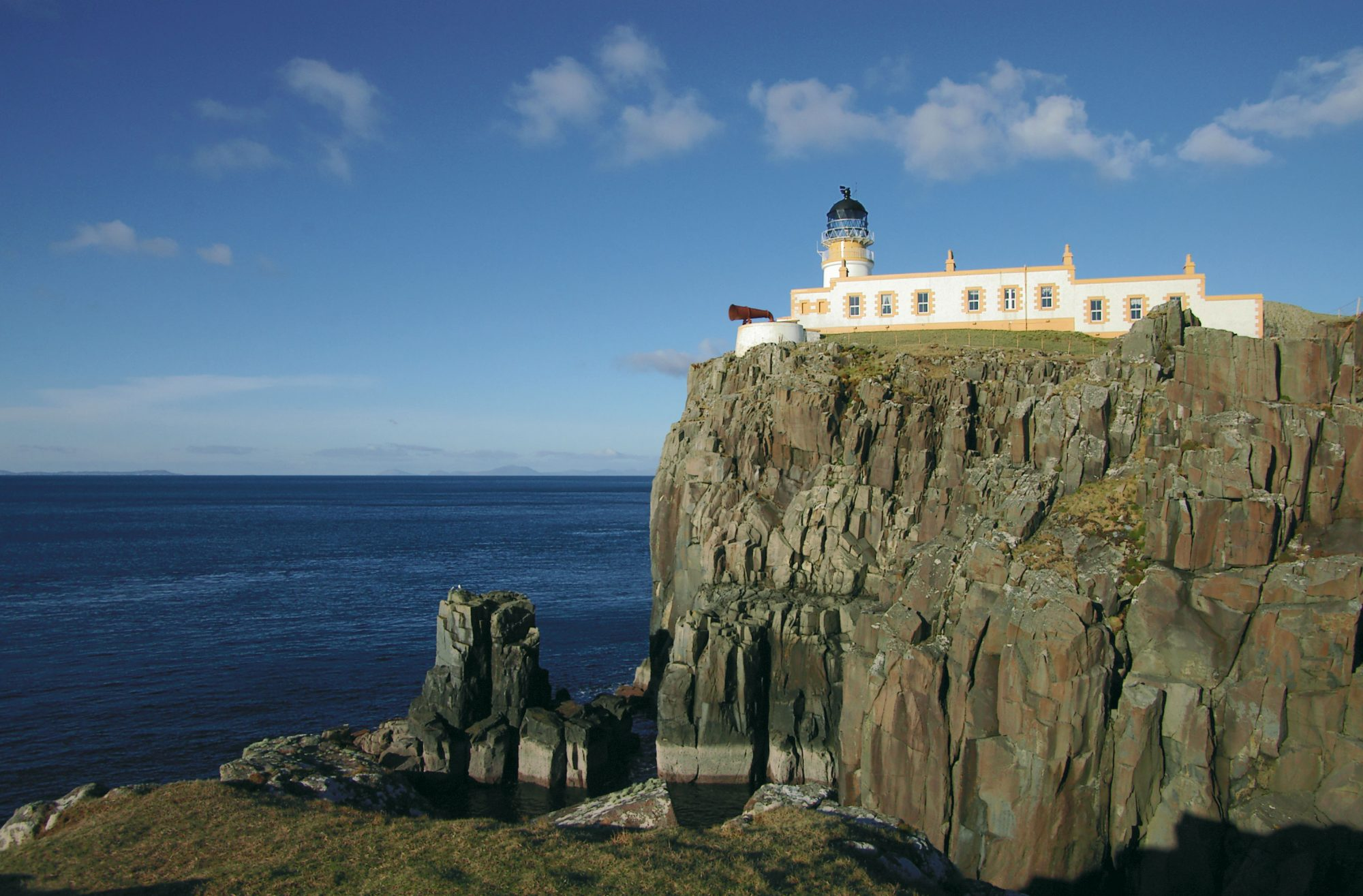 neist point lighthouse on a cliff with a water backdrop