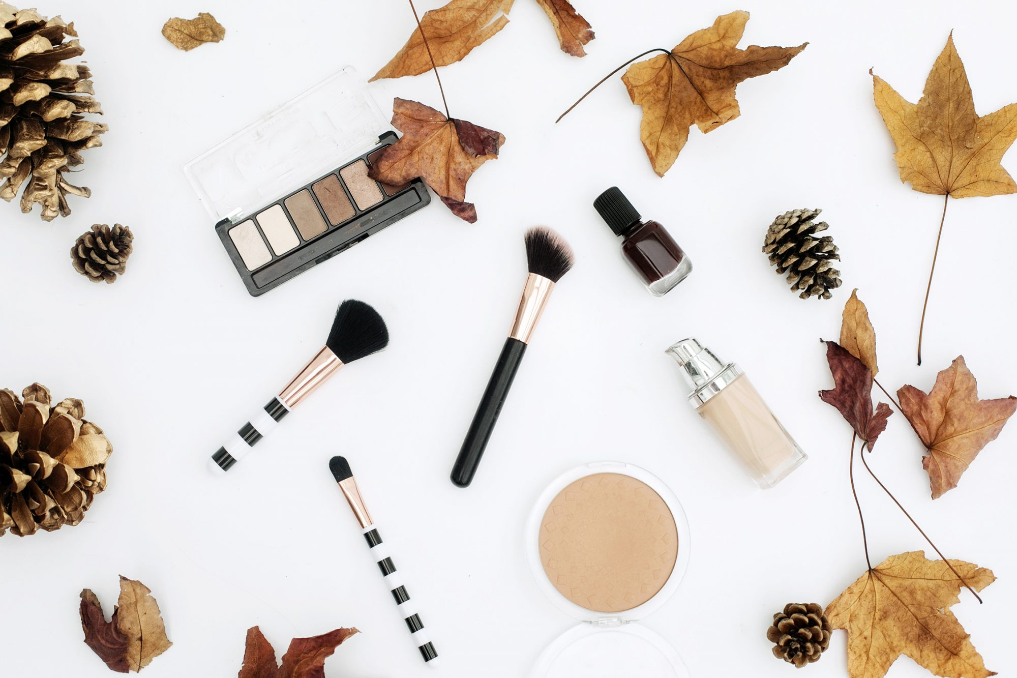 Workspace with cosmetics, lipstick and fall leaves