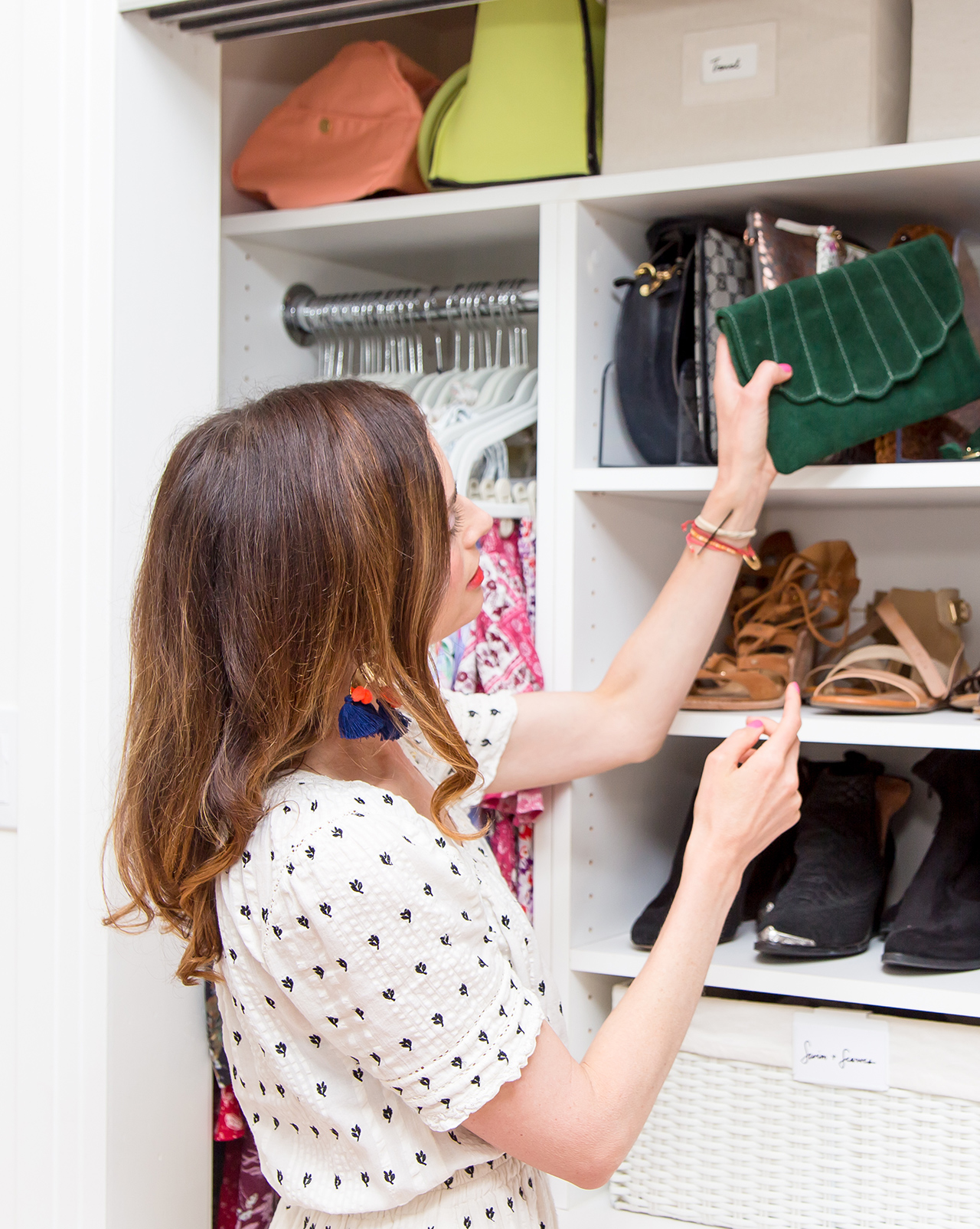 woman organizing bags onto closet shelves