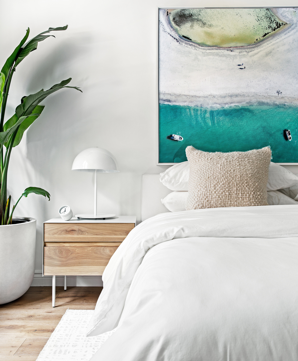 white bedroom theme with plant and wall hanging pop of color
