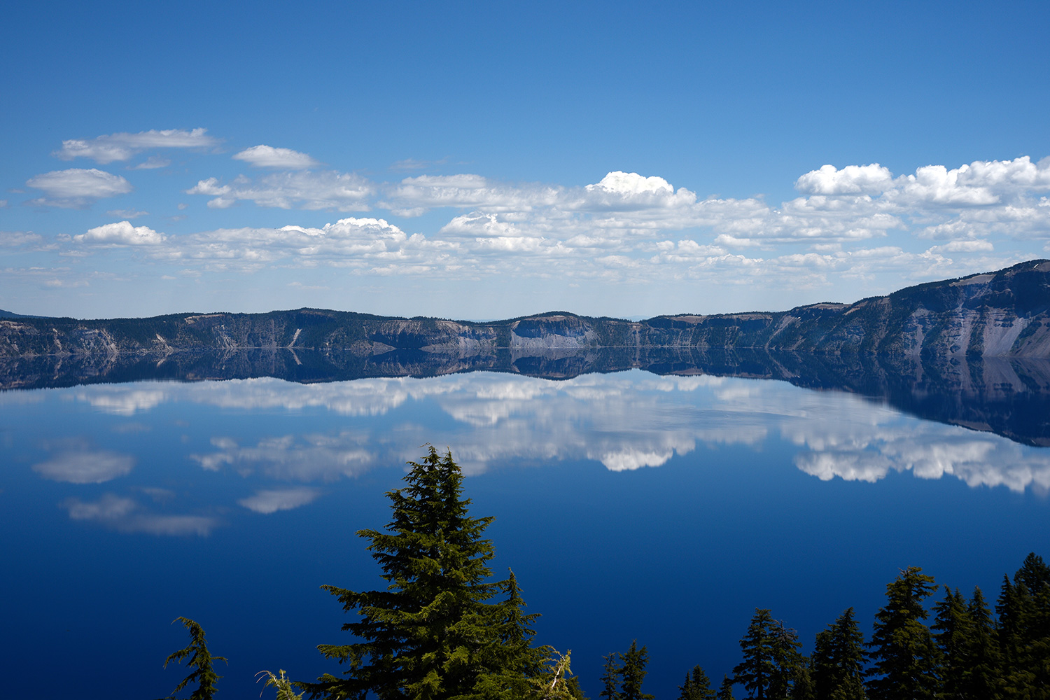 Clouds are reflected in Crater Lake in a view from a scenic overlook on the rim of the lake in Crater Lake National Park in Oregon. The lake, a water-filled caldera of an ancient volcano, was formed 7,700 years ago by the collapse of the volcano Mount Mazama.