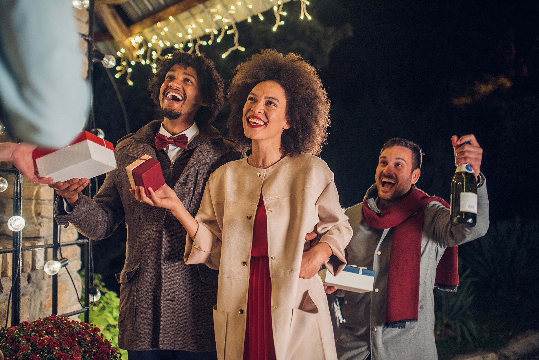 Three people looking up with gifts in hand