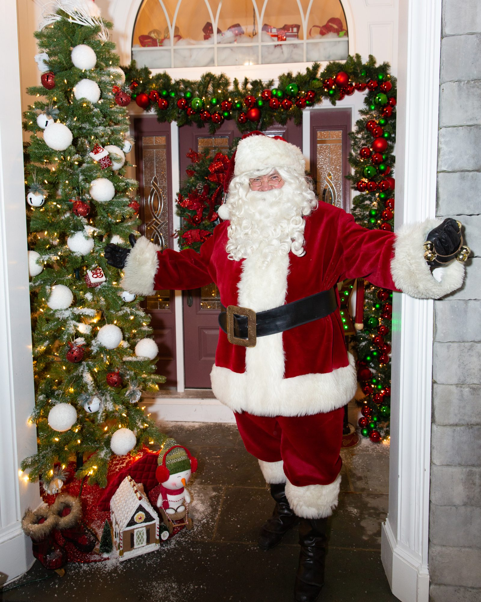 santa claus posing in front of door with holiday decor