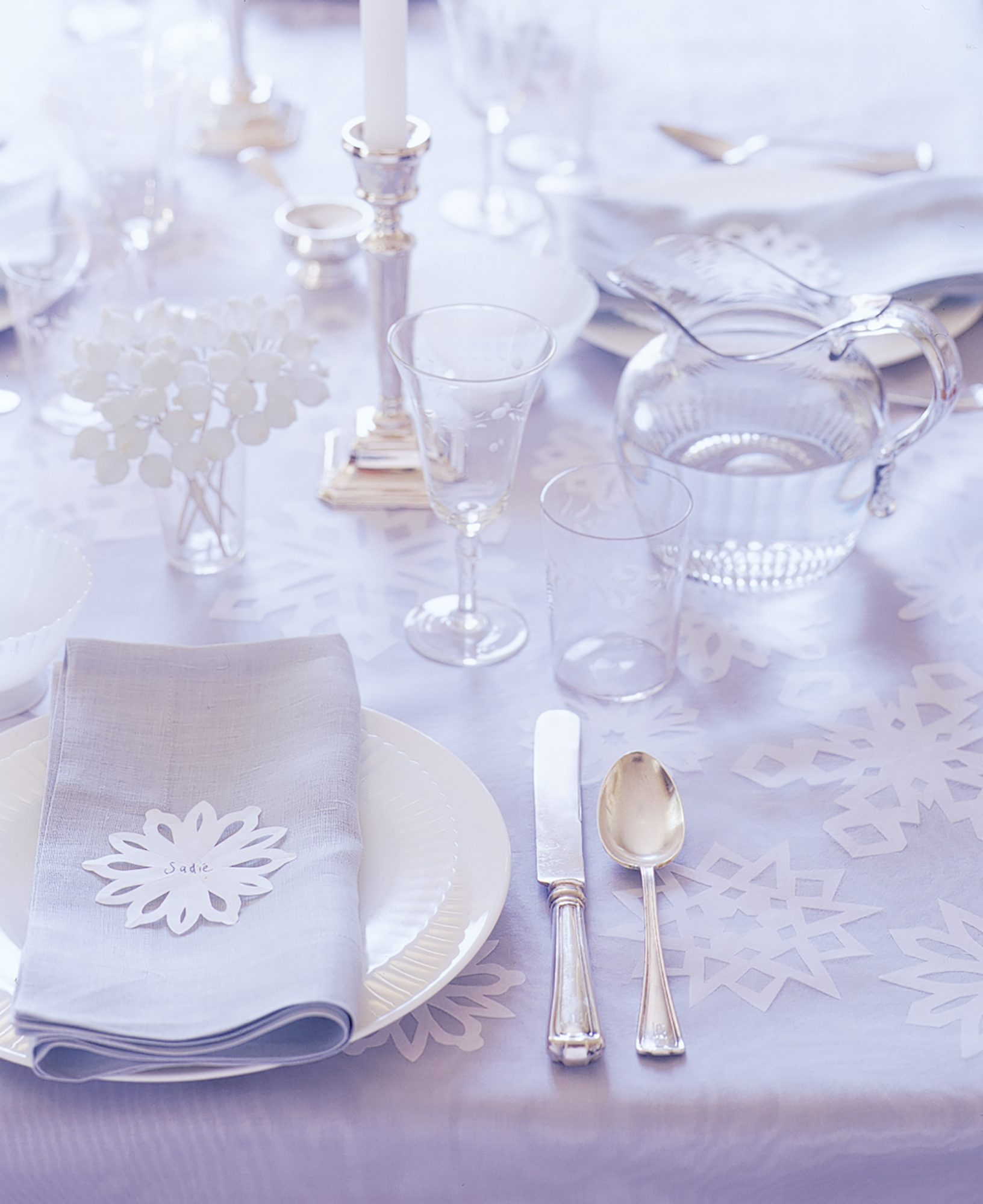 A holiday dinner table evokes drifts of snow when adorned with paper versions beneath your holiday spread. You can also create smaller versions of the same snowflake pattern to use as place cards upon each setting on the table.