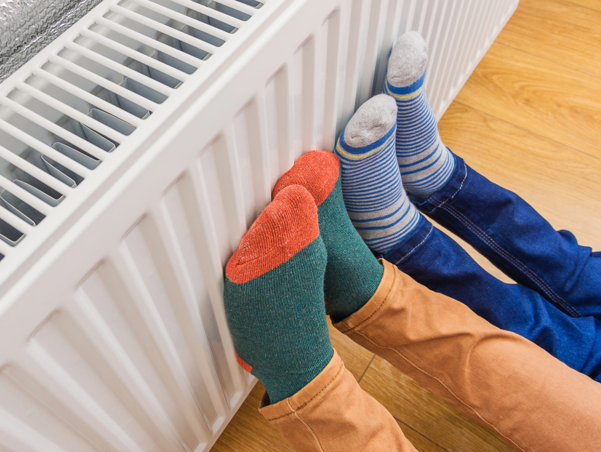 Parent and Child Wearing Socks, Keeping Feet Warm on Radiator
