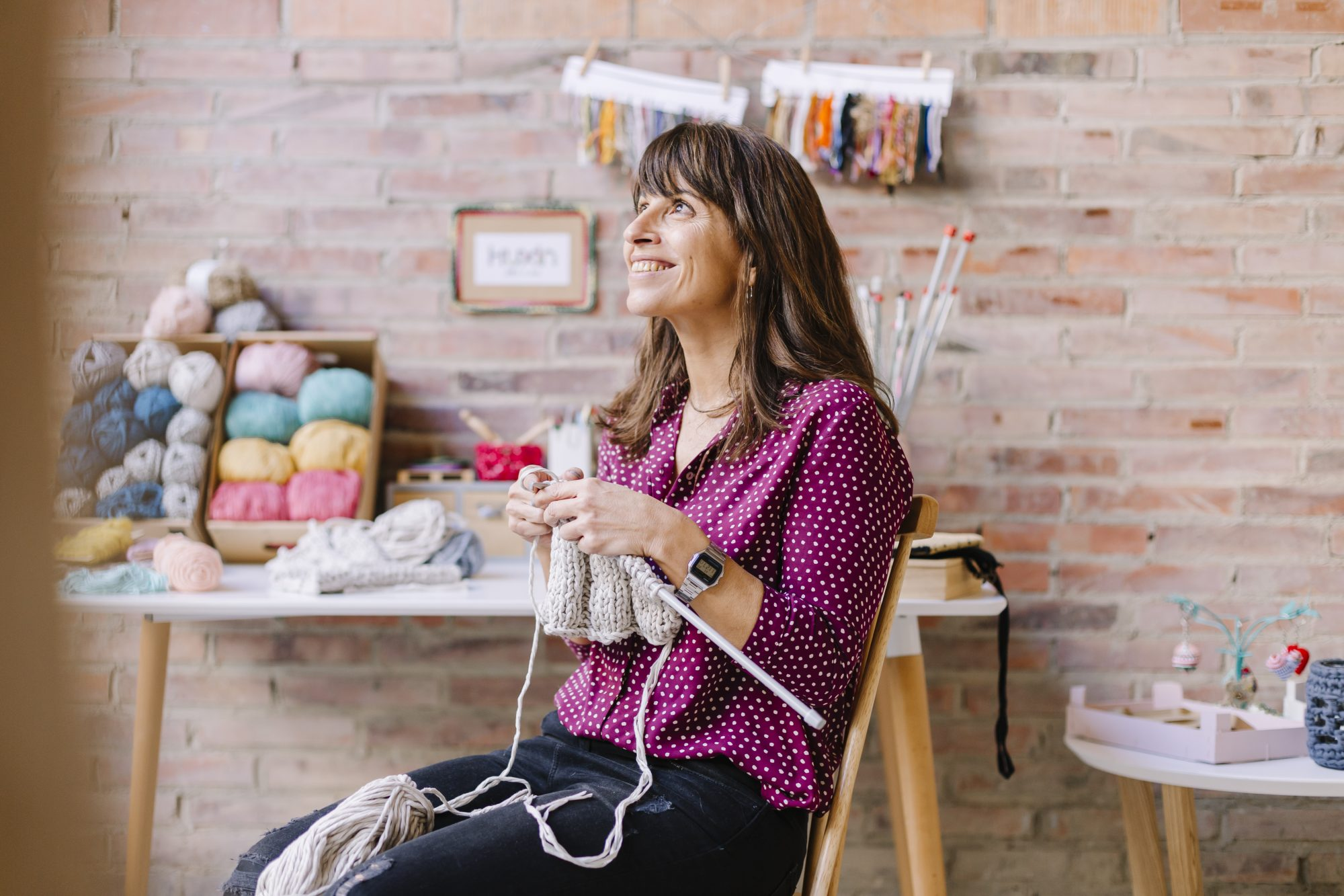 smiling woman sitting on chair knitting